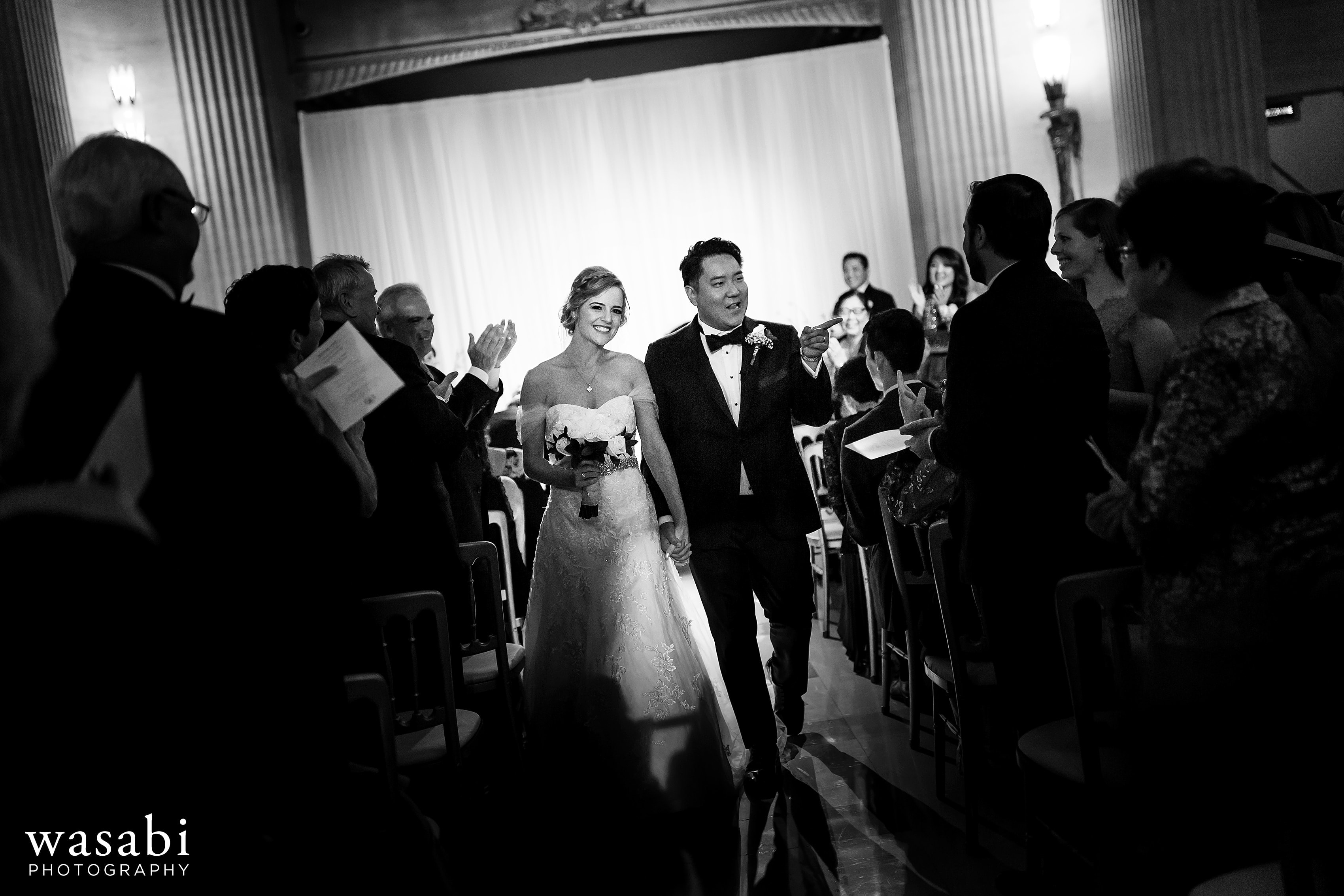 bride and groom walk down the aisle after Civic Opera House wedding in Chicago