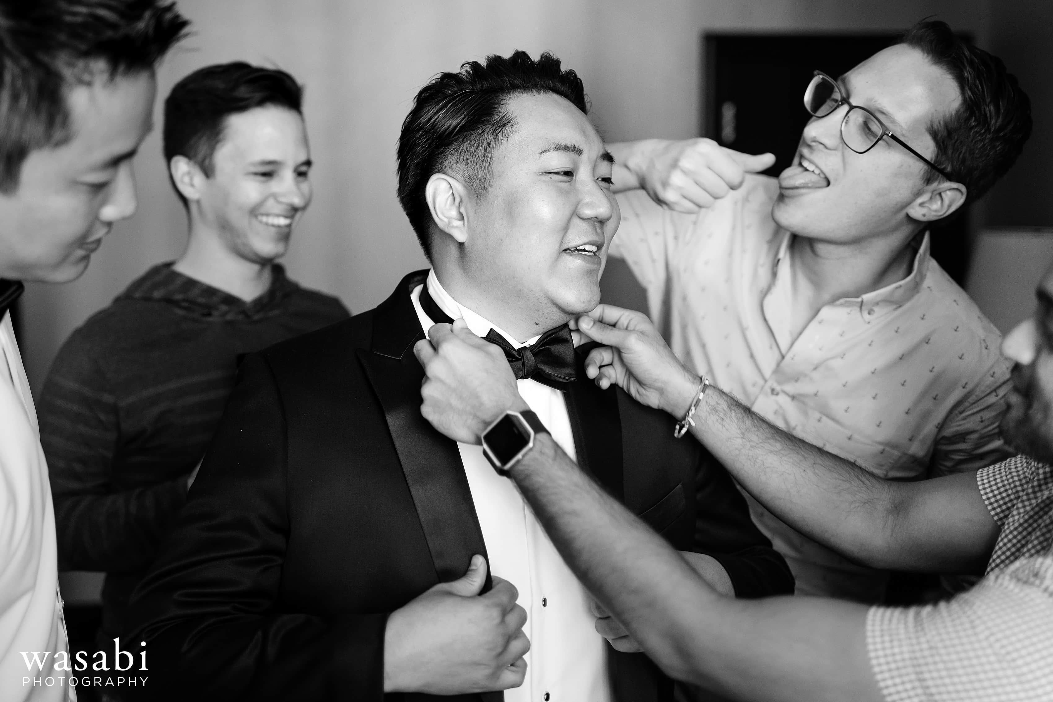 groomsmen help groom adjust bowtie while getting ready for wedding