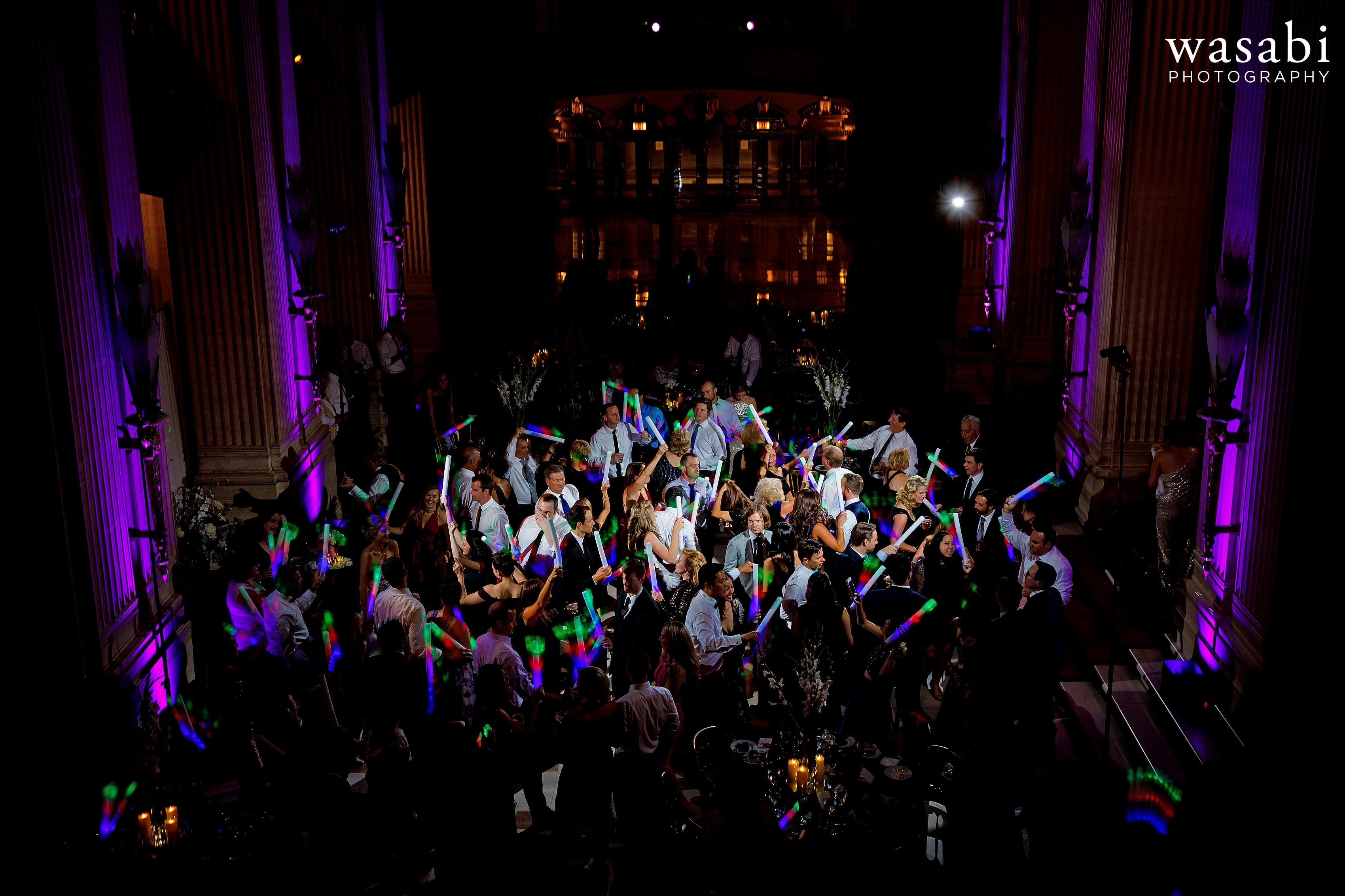 guests wave multicolor foam glow sticks on dance floor during wedding reception at Civic Opera House