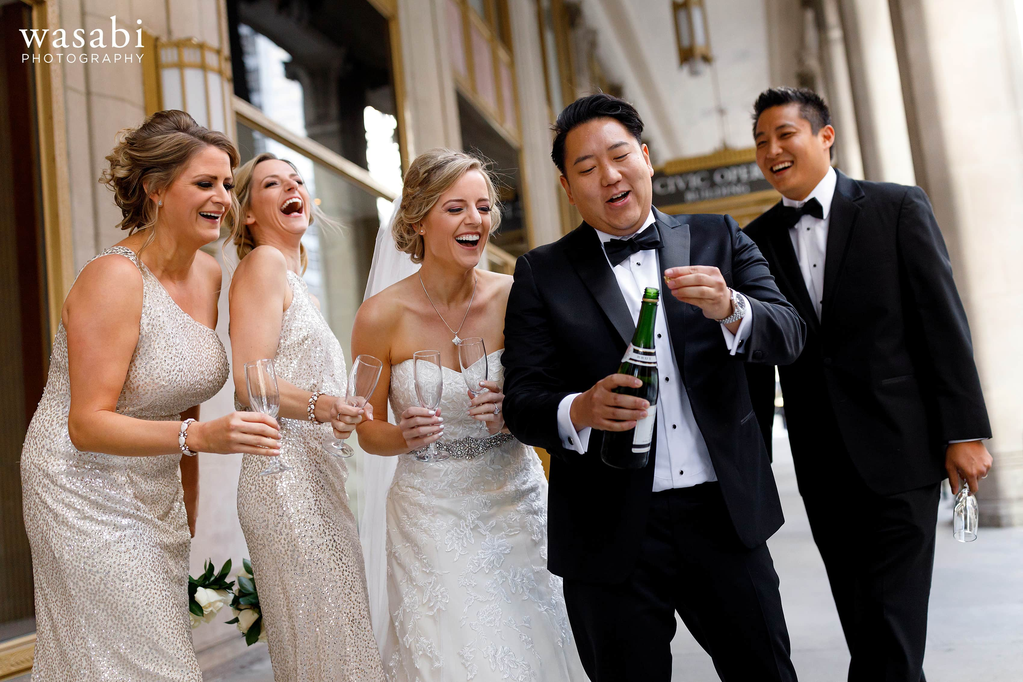 wedding party laughs as groom pops bottle of champagne outside Civic Opera House in Chicago