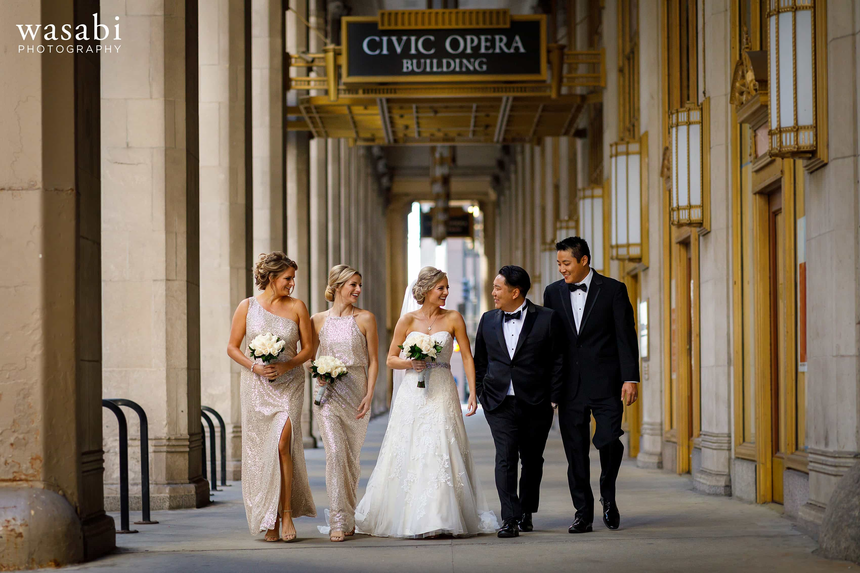 wedding party laughs while walking under overhang at Civic Opera House in Chicago