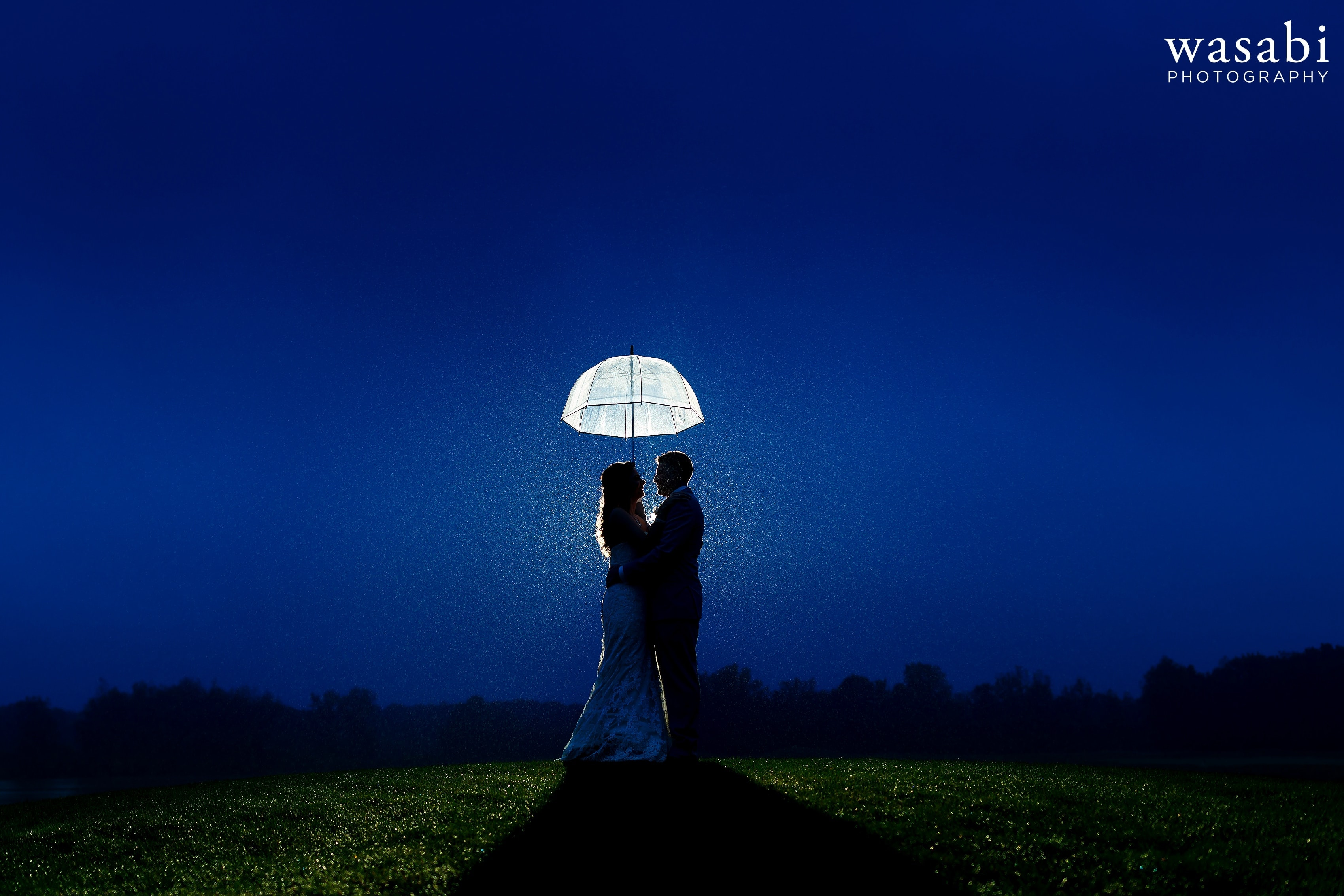 Backlit photo in the rain of bride and groom on a hill with blue sky under umbrella at Buck's Run Golf Club wedding photos in Mount Pleasant, Michigan.