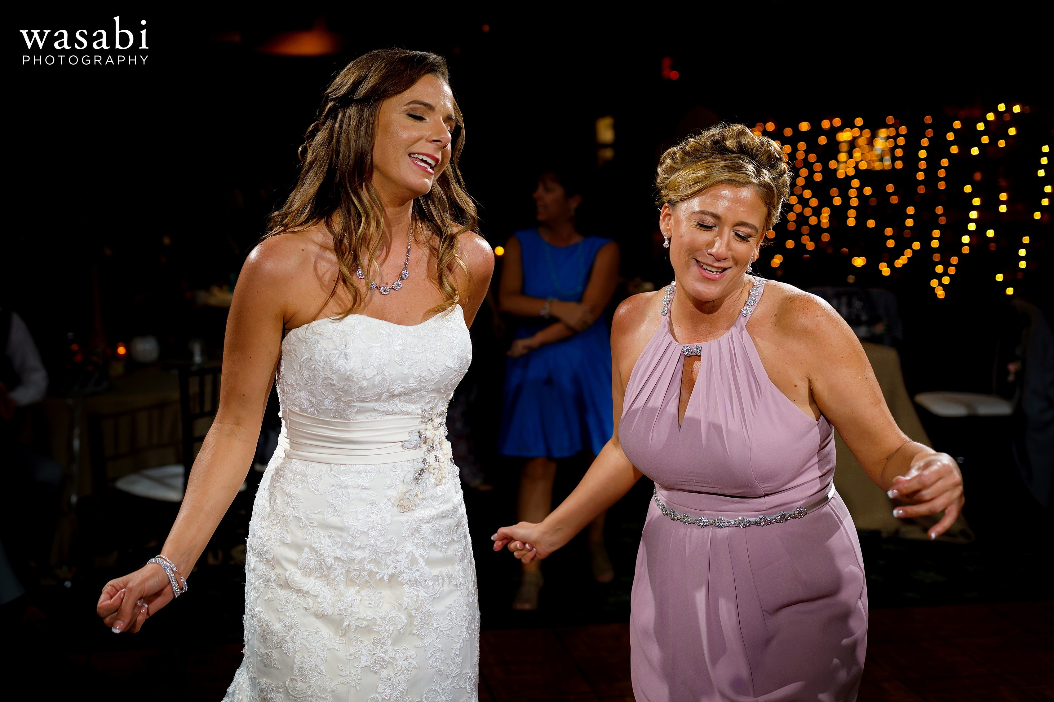 Bride and bridesmaid on the dance floor during Buck's Run Golf Club wedding reception in Mount Pleasant, Michigan.