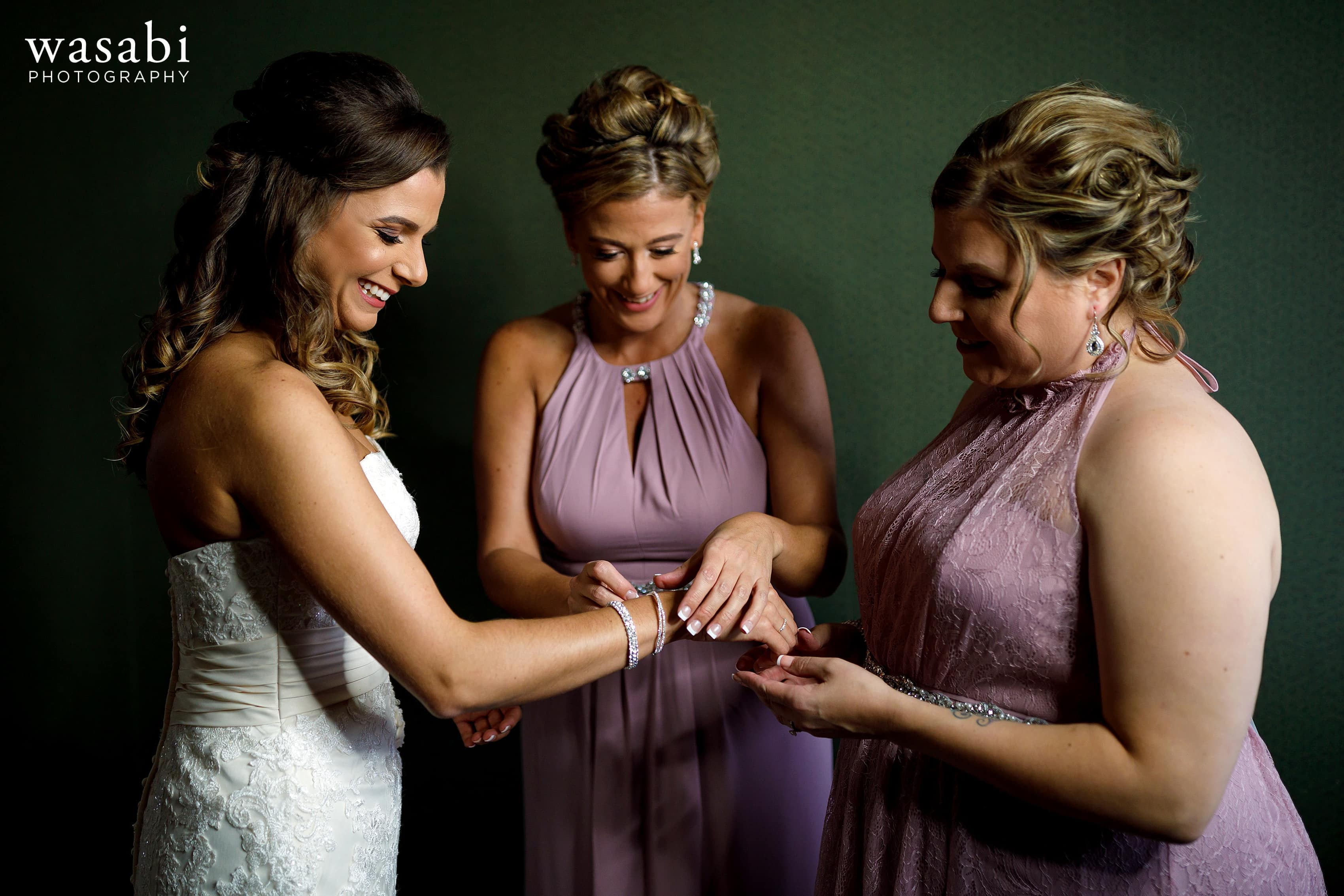 Bride and bridesmaids put jewelry on while getting ready for wedding at Buck's Run Golf Club in Mount Pleasant, Michigan.