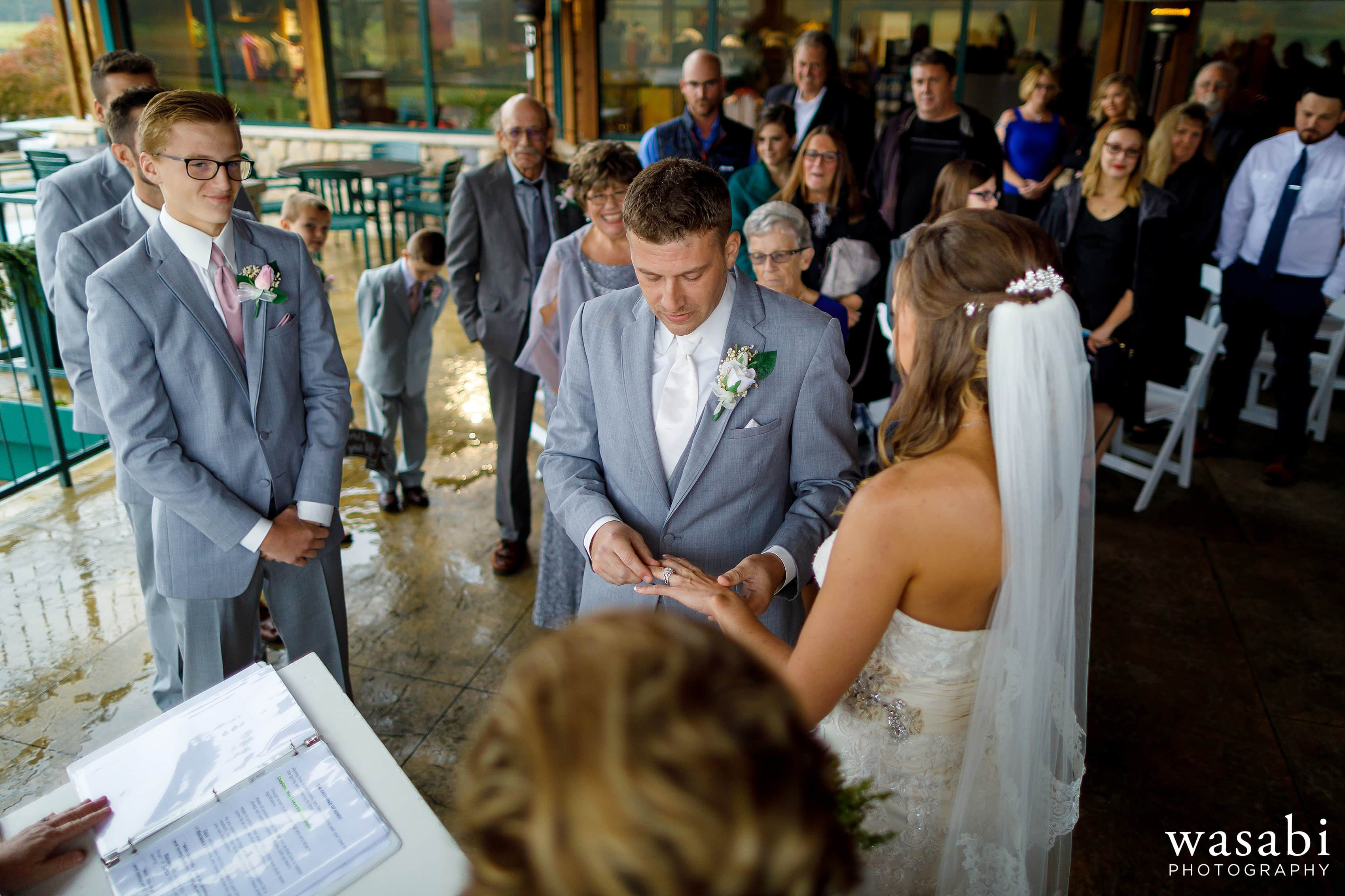 Bride and groom exchange rings during Buck's Run Golf Club wedding ceremony in Mount Pleasant, Michigan.