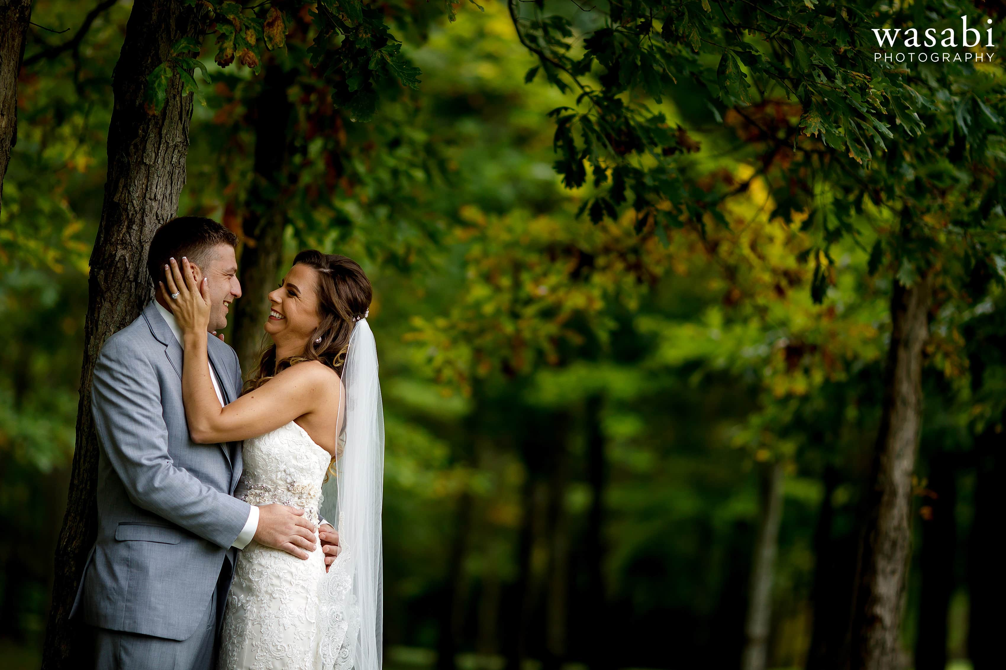 Bride and groom pose for portraits in front of fall color at Buck's Run Golf Club in Mount Pleasant, Michigan.