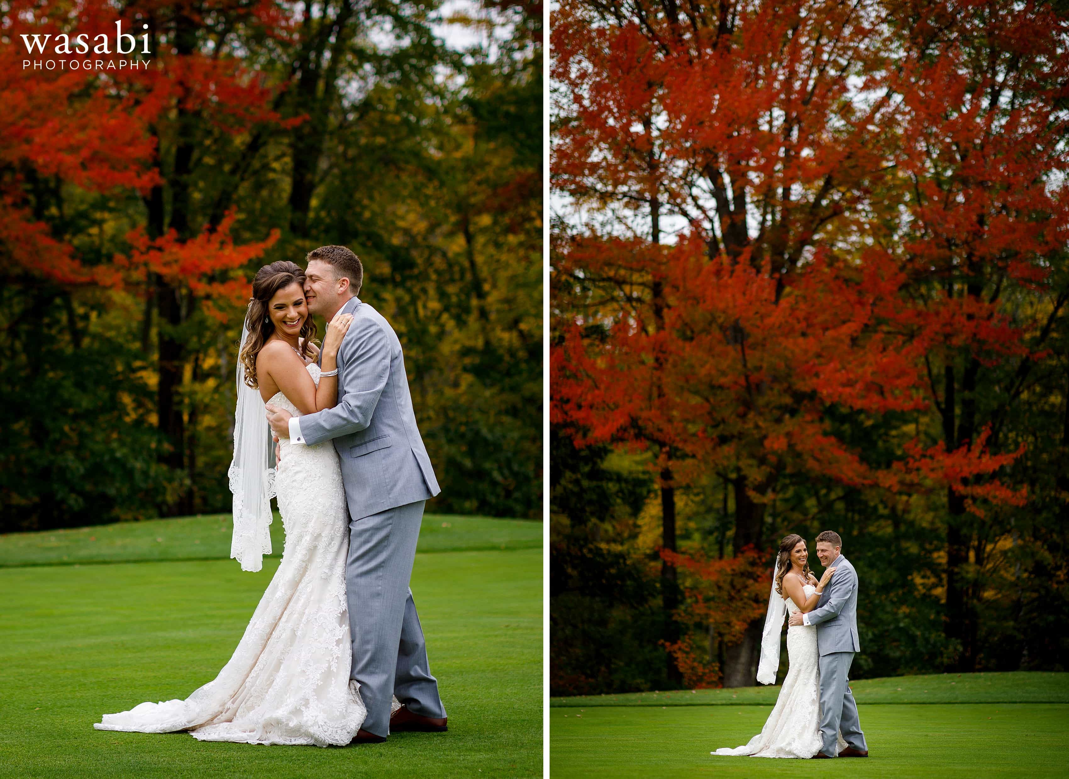 Bride and groom pose for portraits in front of fall color red trees at Buck's Run Golf Club in Mount Pleasant, Michigan.