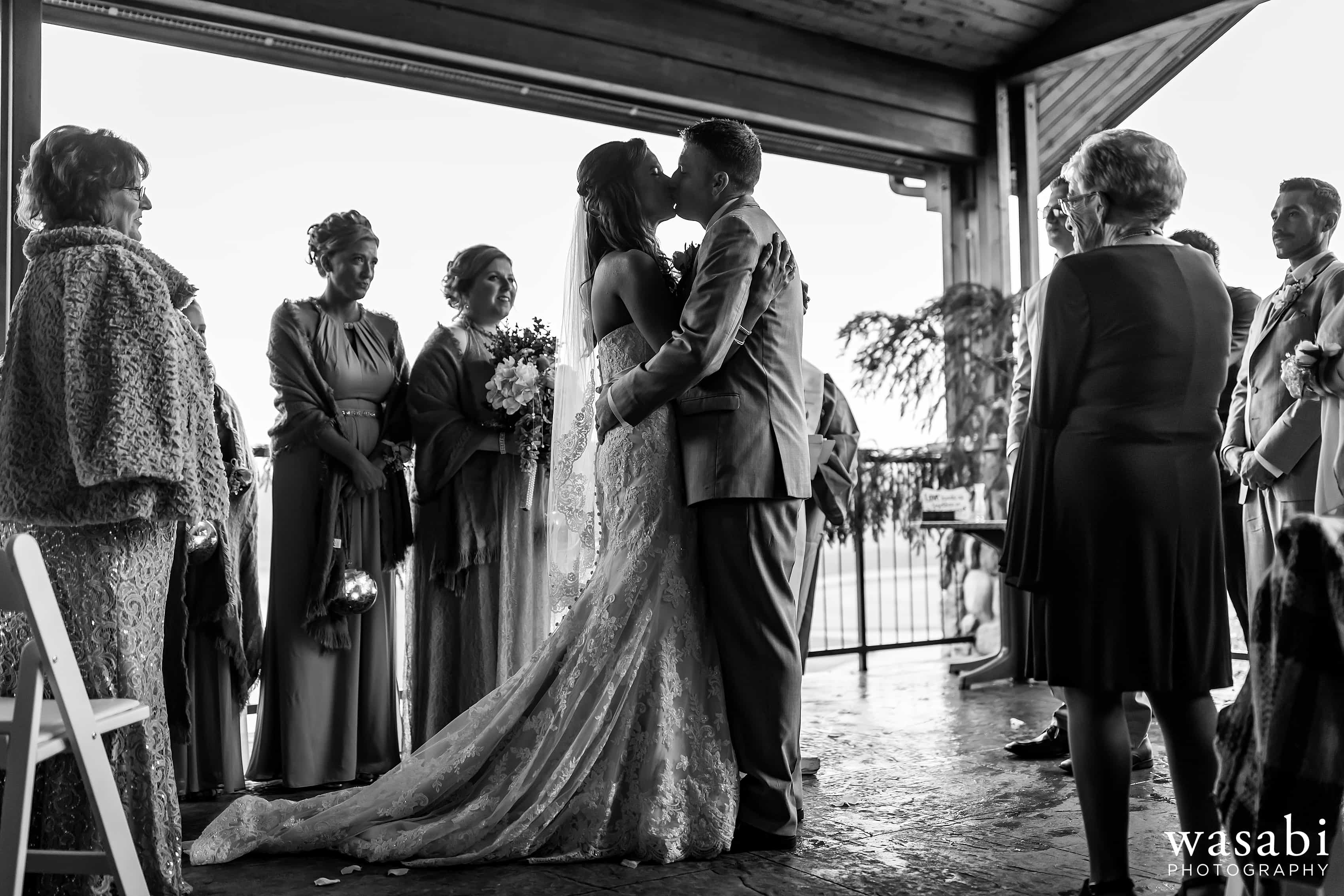 Bride and groom share a first kiss during Buck's Run Golf Club wedding ceremony in Mount Pleasant, Michigan.