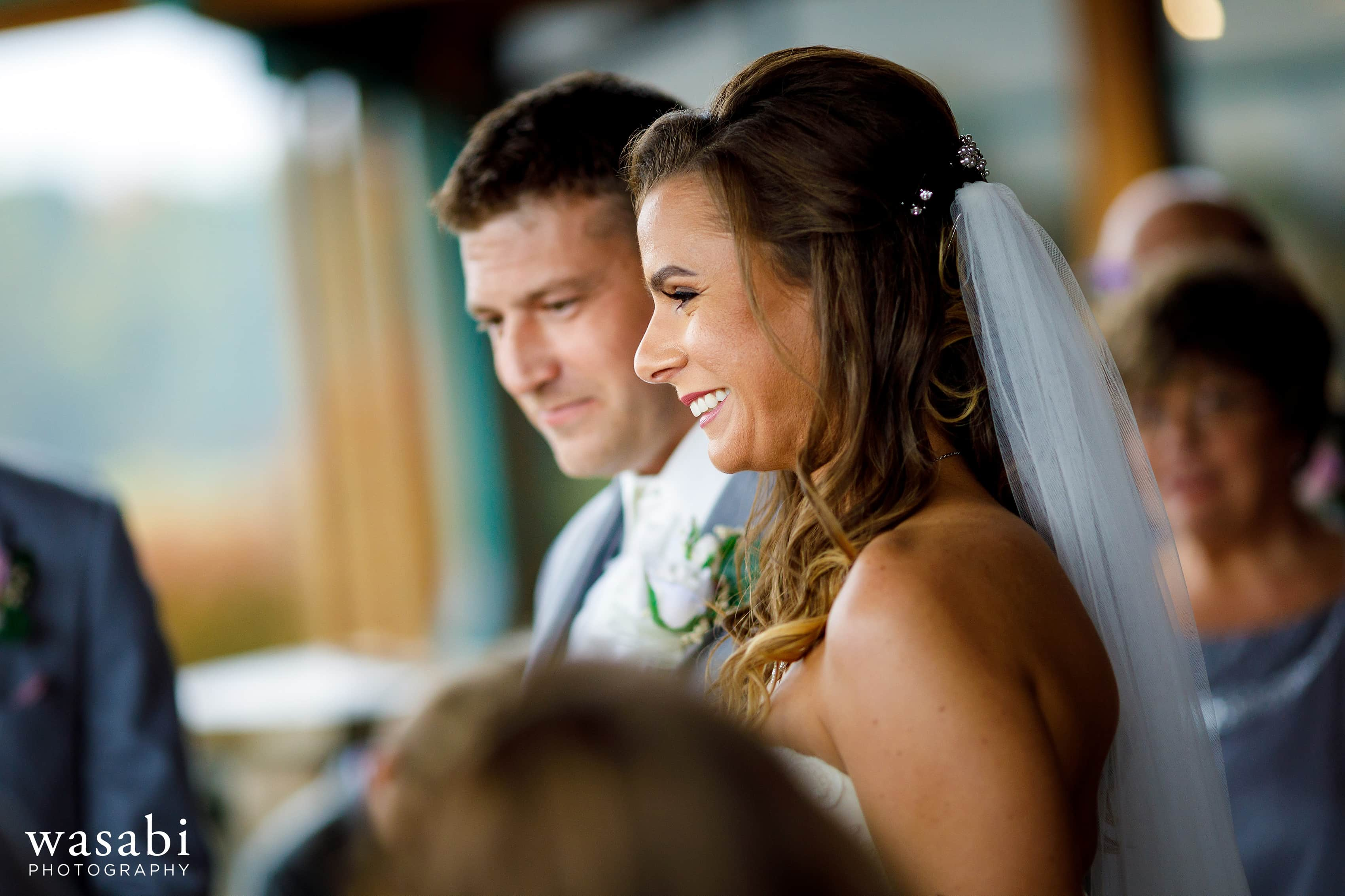 Bride and groom smile during Buck's Run Golf Club wedding ceremony in Mount Pleasant, Michigan.