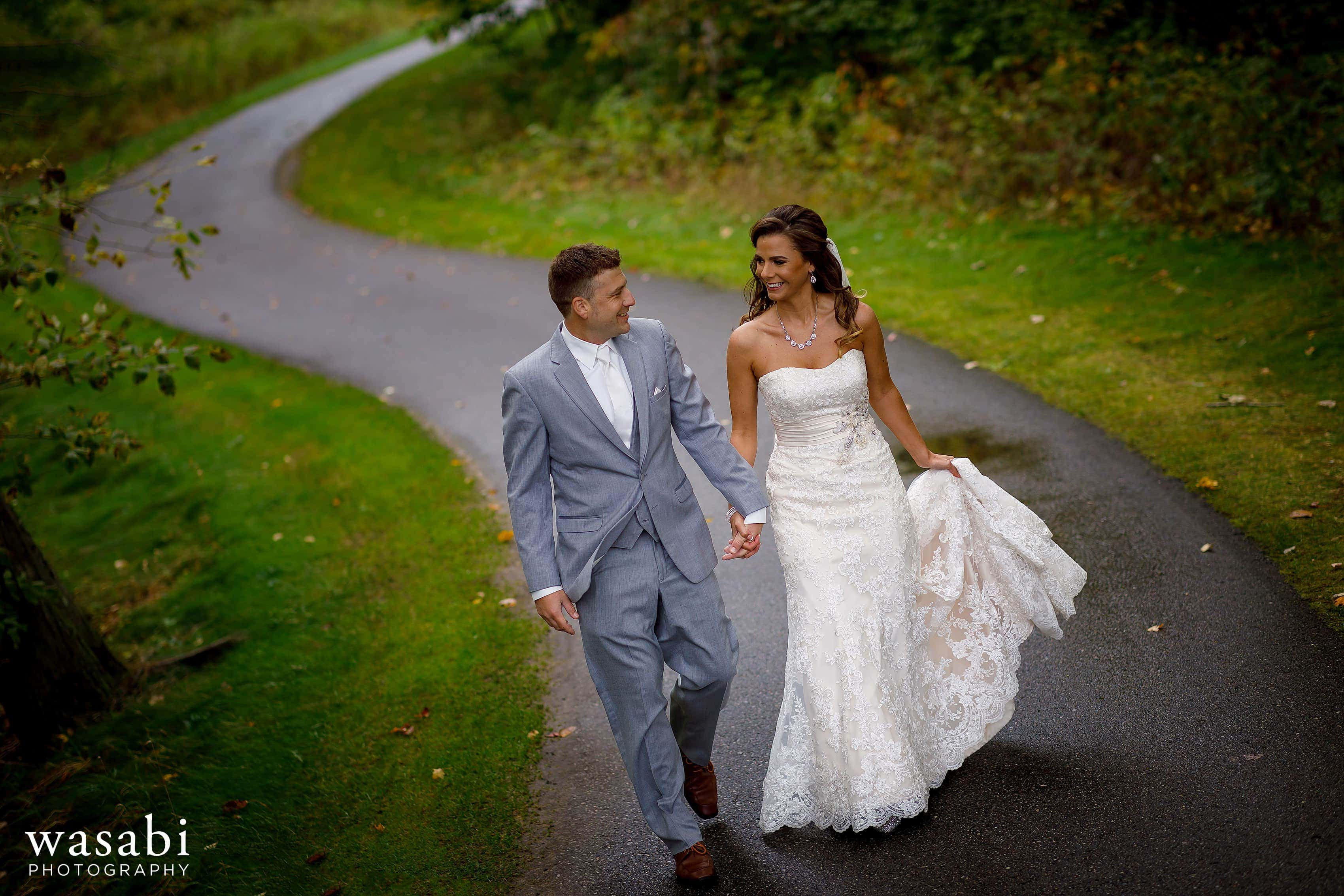 Bride and groom walk down windy road at Buck's Run Golf Club in Mount Pleasant, Michigan.