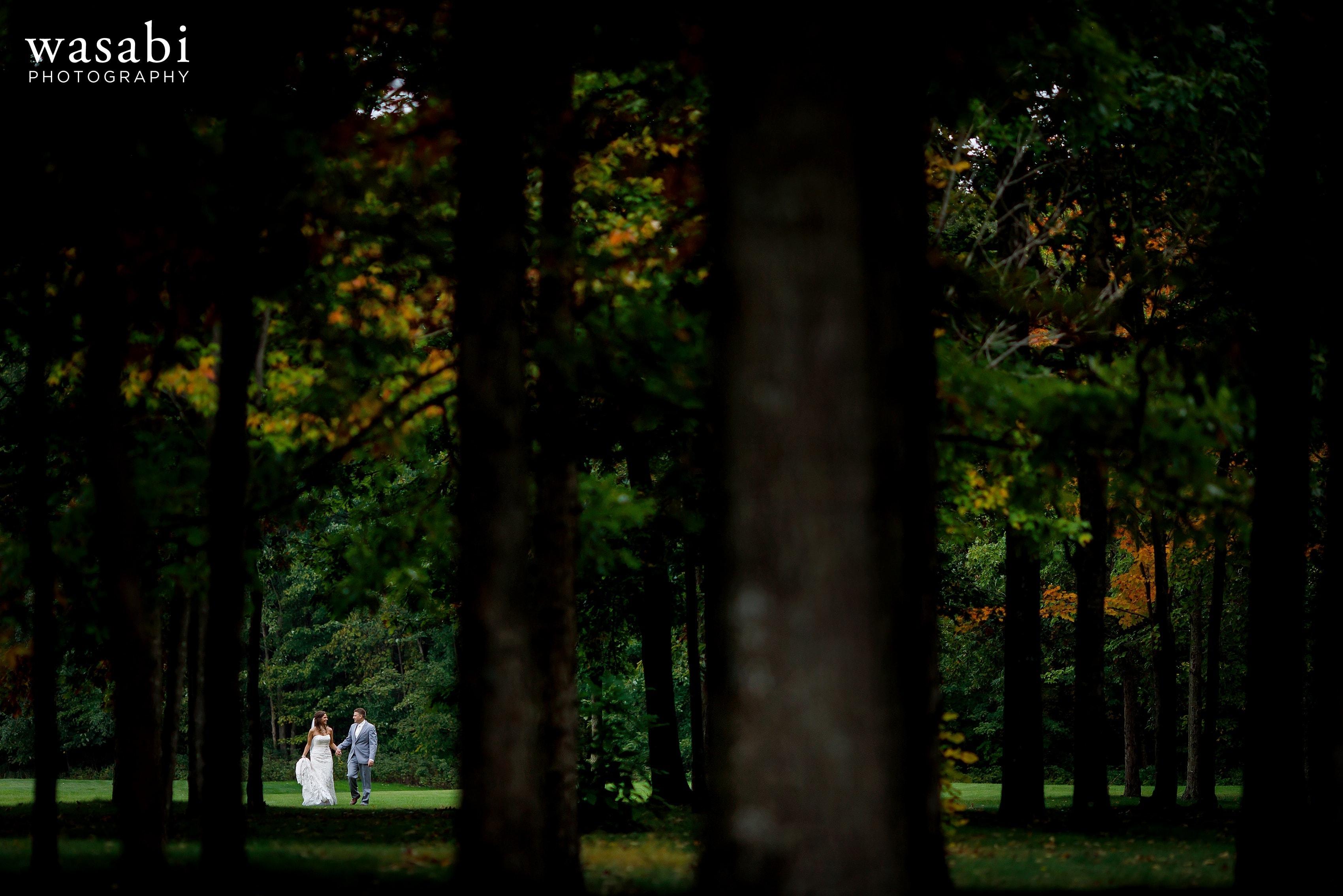 Bride and groom walk through trees before wedding at Buck's Run Golf Club in Mount Pleasant, Michigan.