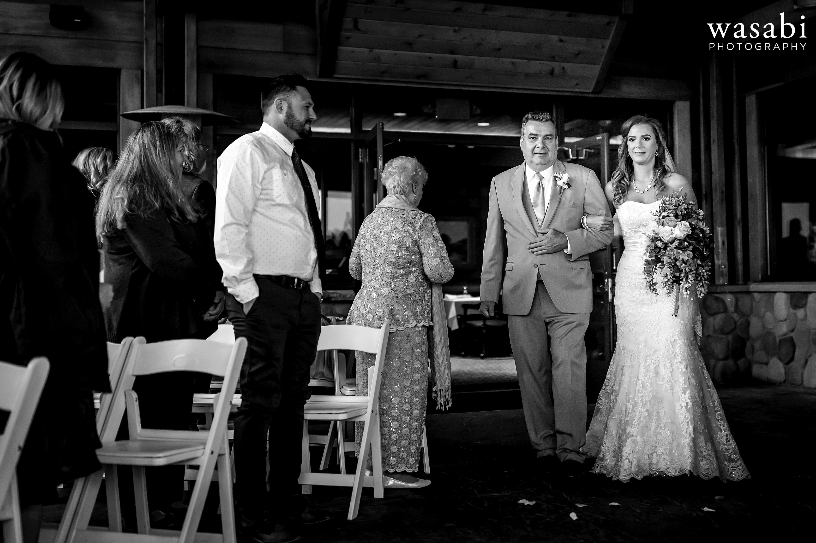 Bride and her father walk down the aisle during Buck's Run Golf Club wedding ceremony in Mount Pleasant, Michigan.