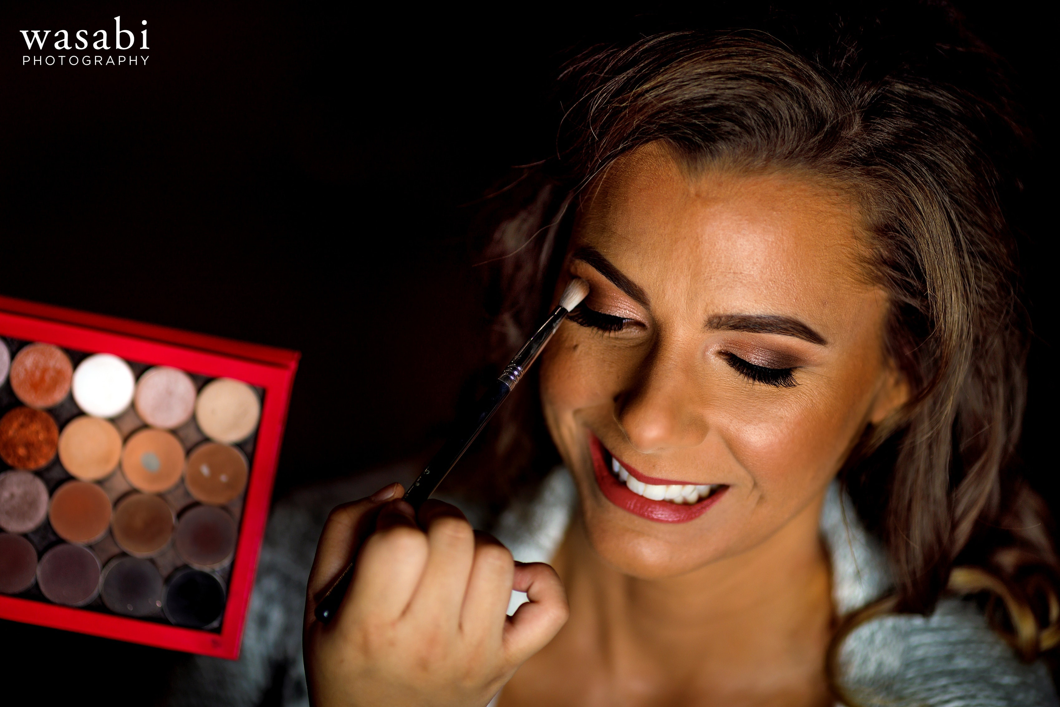 Bride has makeup applied while getting ready for wedding at Buck's Run Golf Club in Mount Pleasant, Michigan.