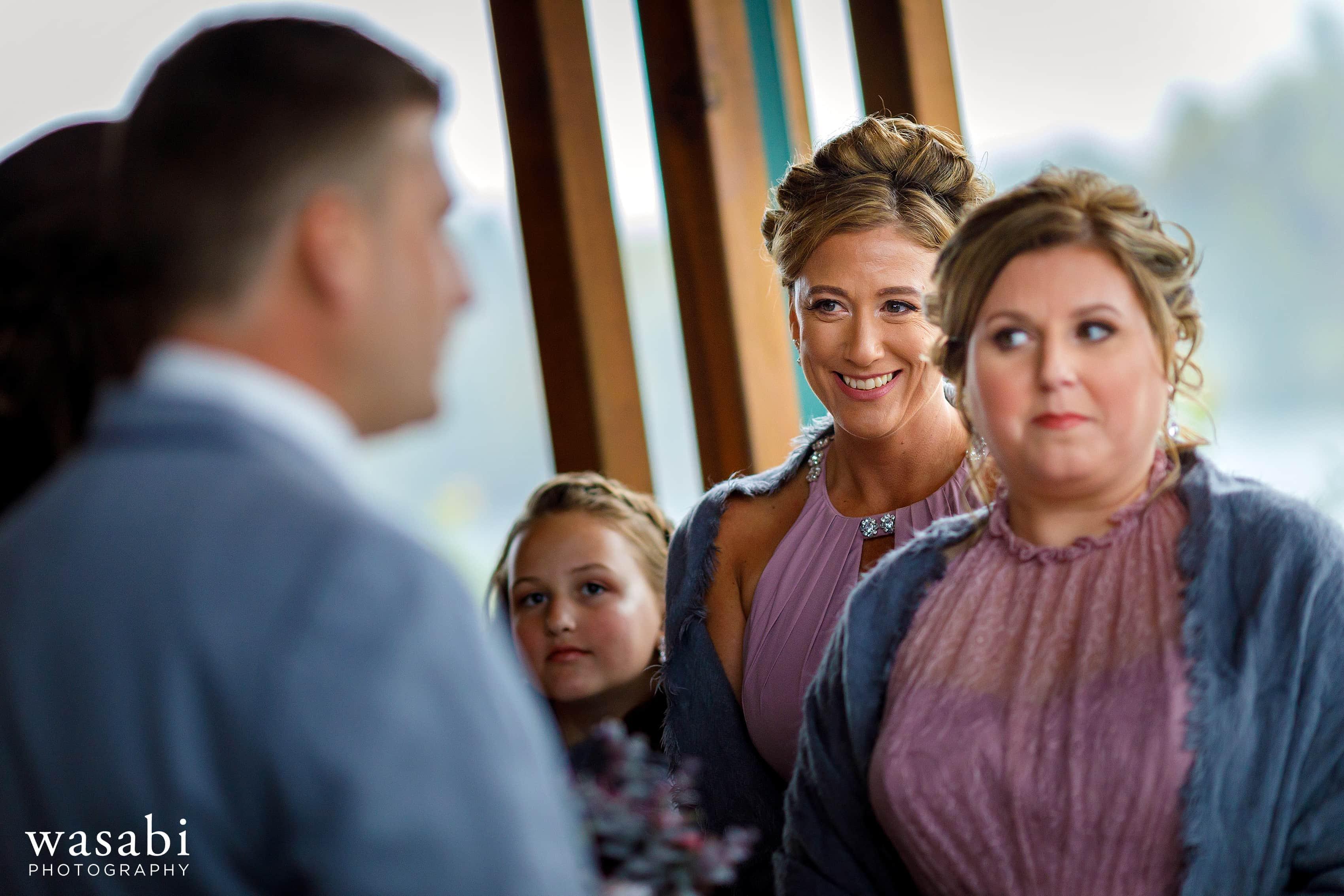 Bridesmaids smile at bride during Buck's Run Golf Club wedding ceremony in Mount Pleasant, Michigan.