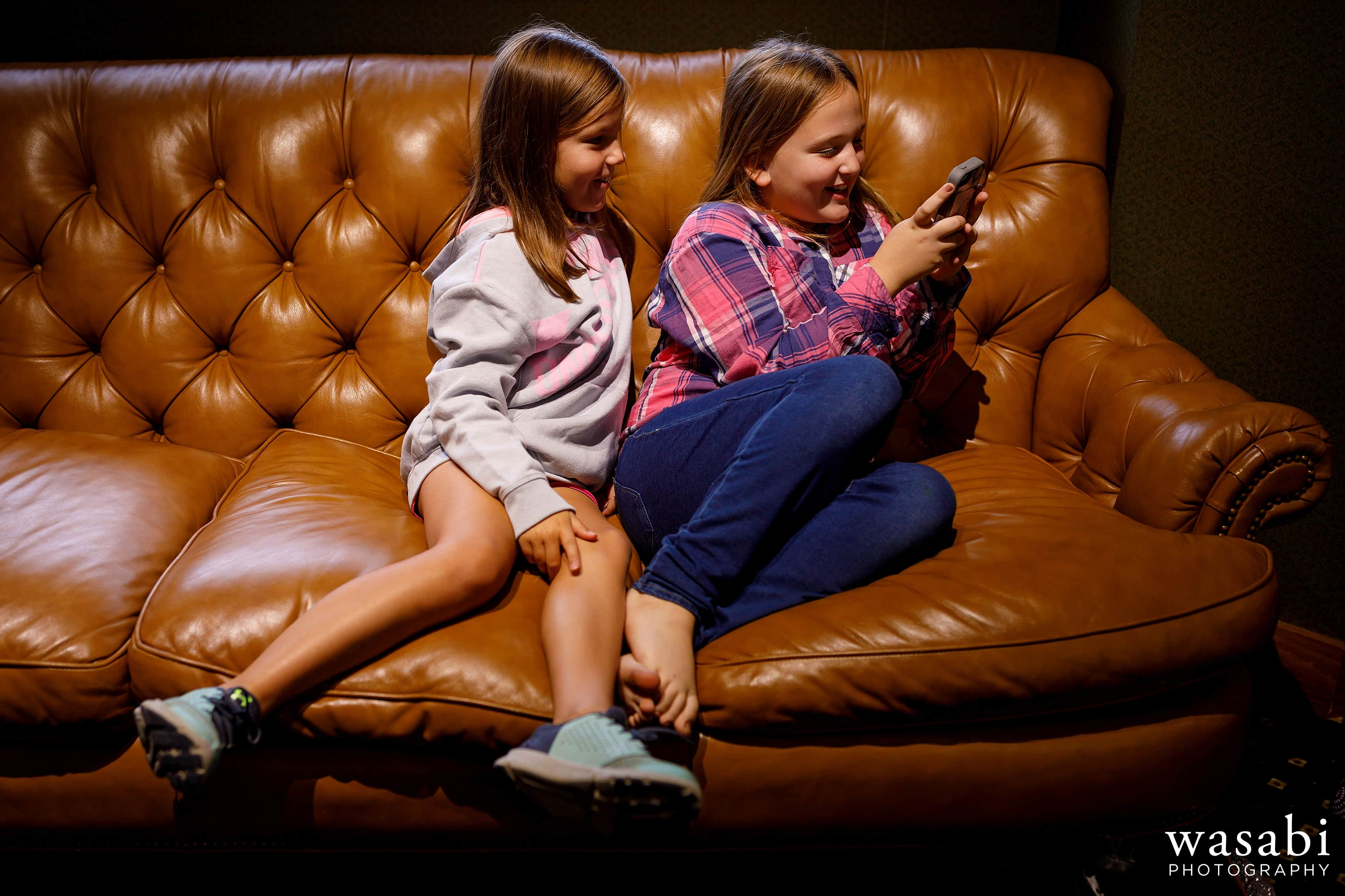 Girls play with an iPhone while getting ready for wedding at Buck's Run Golf Club in Mount Pleasant, Michigan.