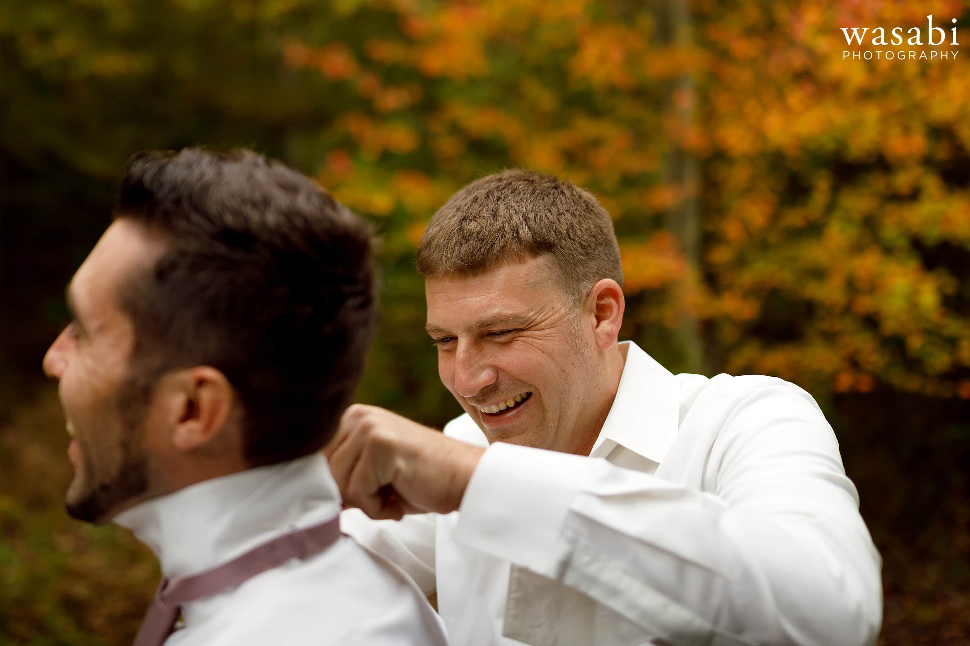 Groom and groomsman adjust ties while getting ready for wedding at Buck's Run Golf Club in Mount Pleasant, Michigan.