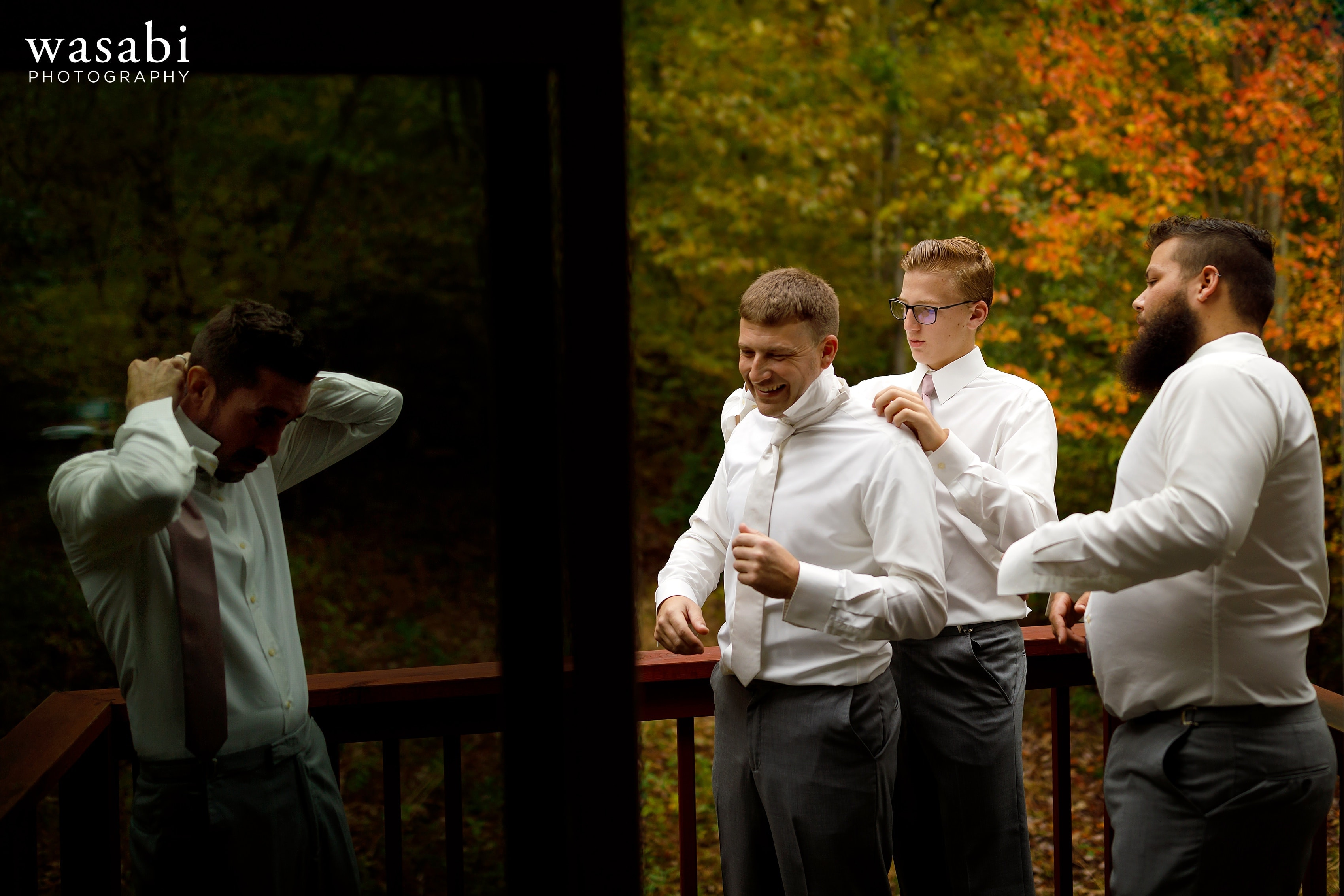 Groom and groomsmen adjust ties while getting ready for wedding at Buck's Run Golf Club in Mount Pleasant, Michigan.