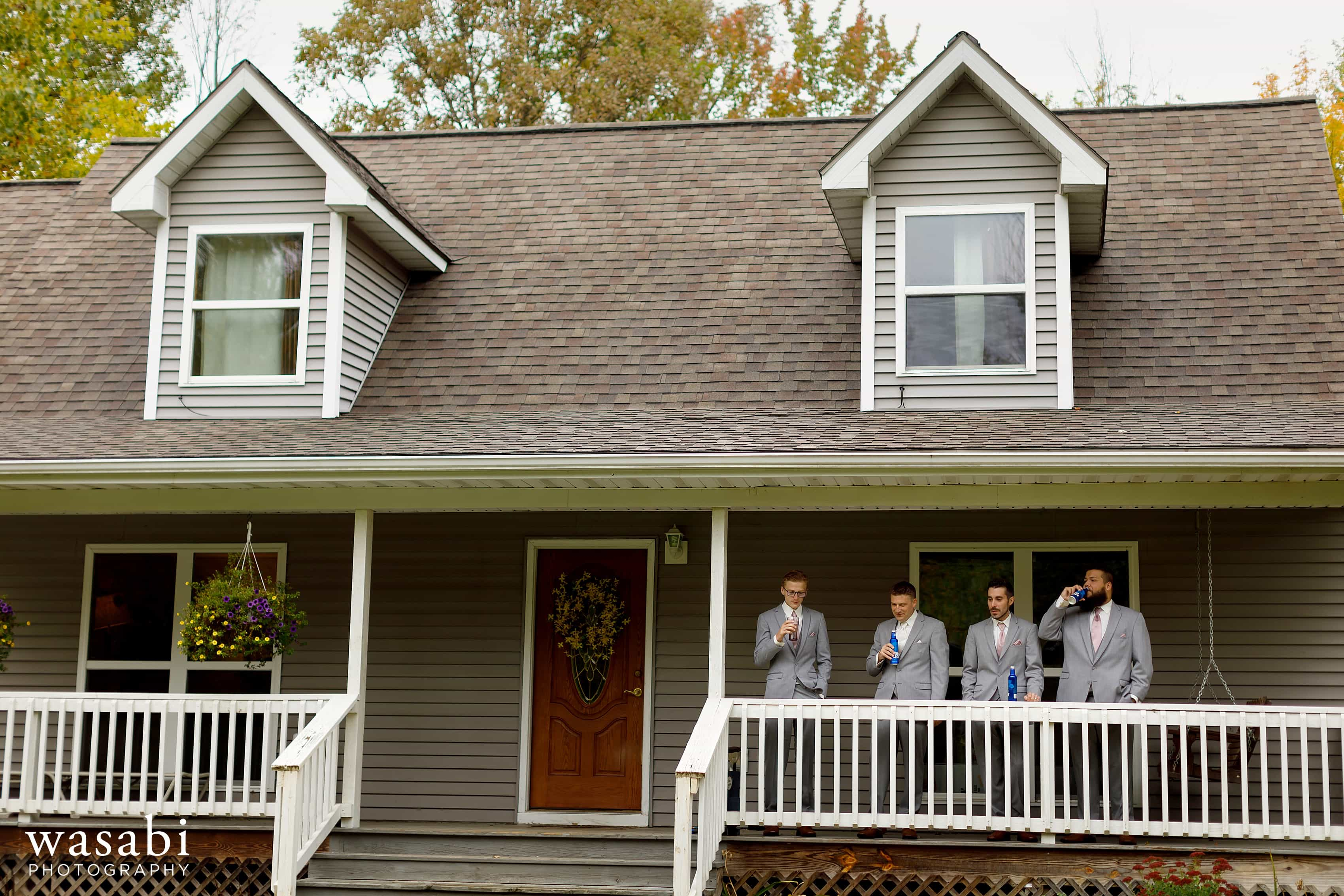 Groom and groomsmen drink on porch while getting ready for wedding at Buck's Run Golf Club in Mount Pleasant, Michigan.