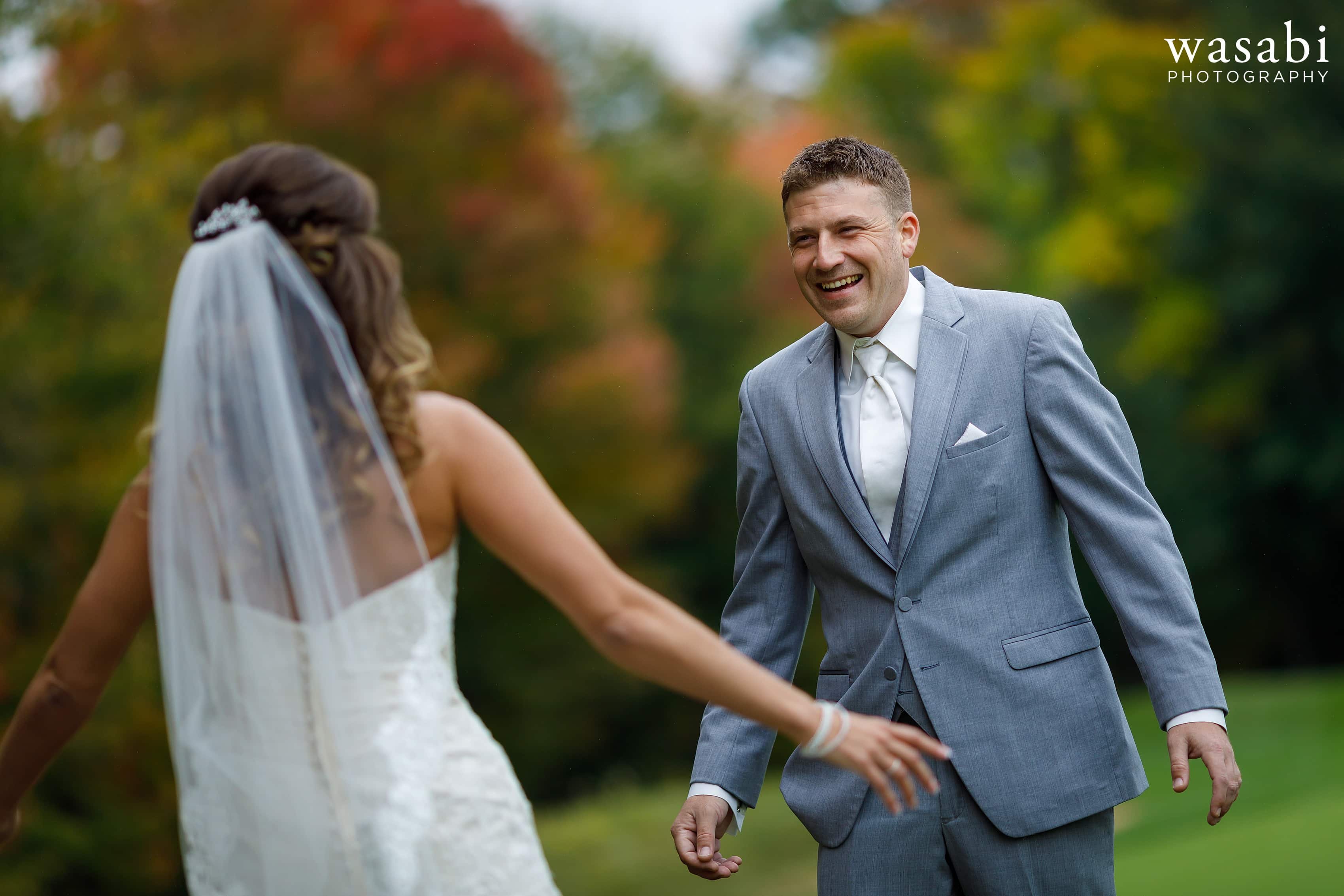 Groom reacts to seeing bride during first look at Buck's Run Golf Club in Mount Pleasant, Michigan.