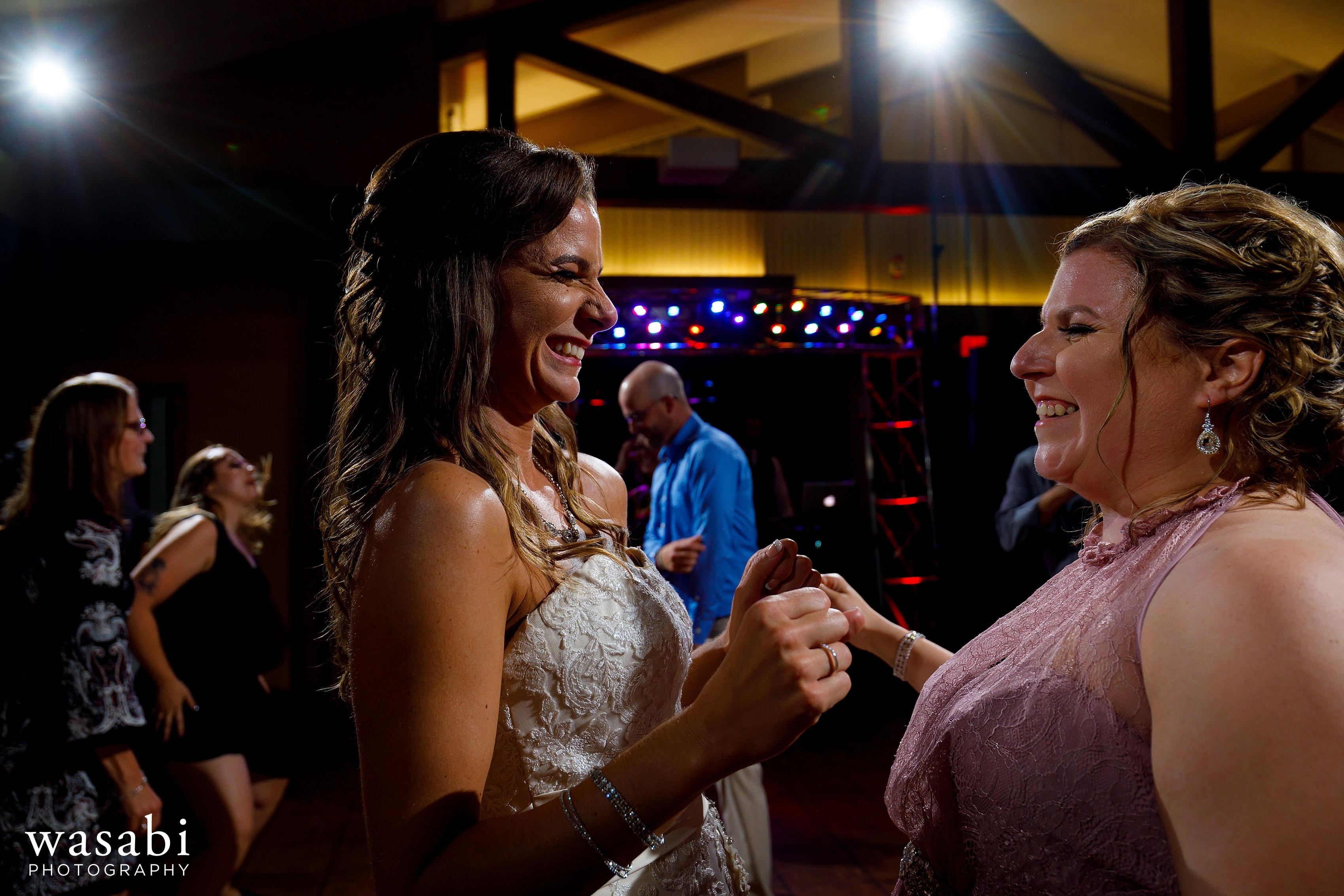 bride and sister on the dance floor during Buck's Run Golf Club wedding reception in Mount Pleasant, Michigan.