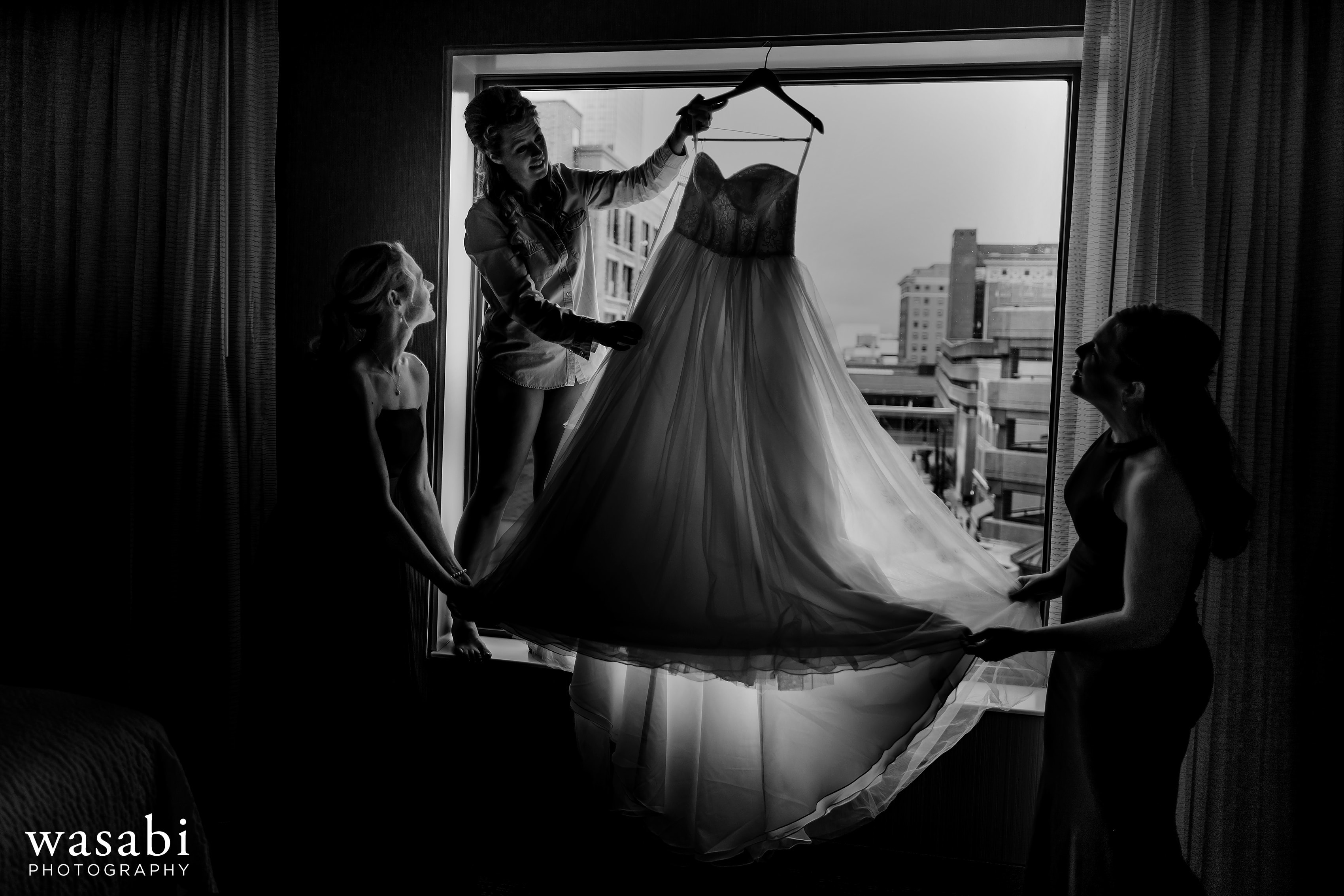 Bride and bridesmaids pull dress down from the window at Courtyard Marriott Downtown Grand Rapids before her wedding
