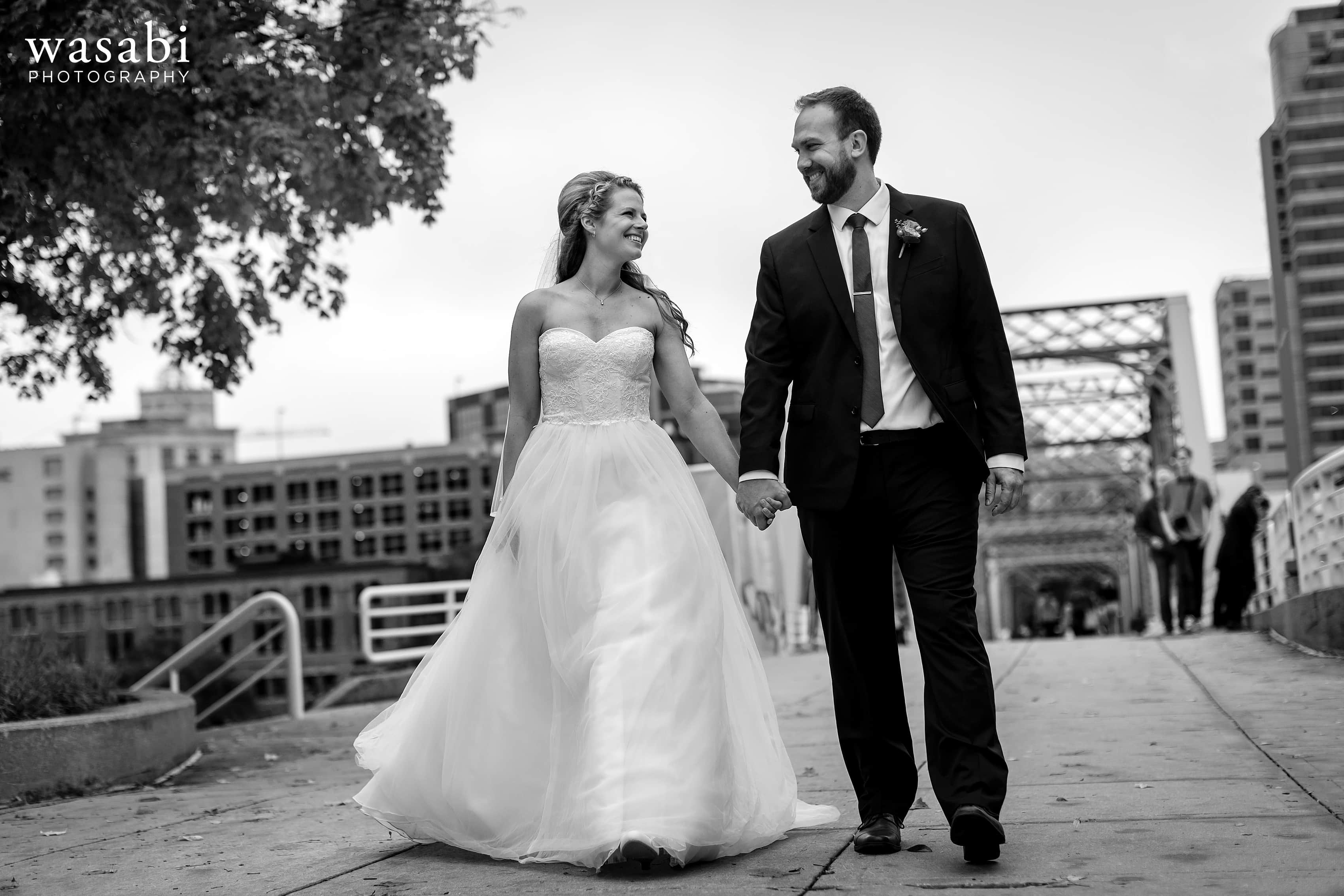 Bride and groom walk across the Blue Bridge in downtown Grand Rapids