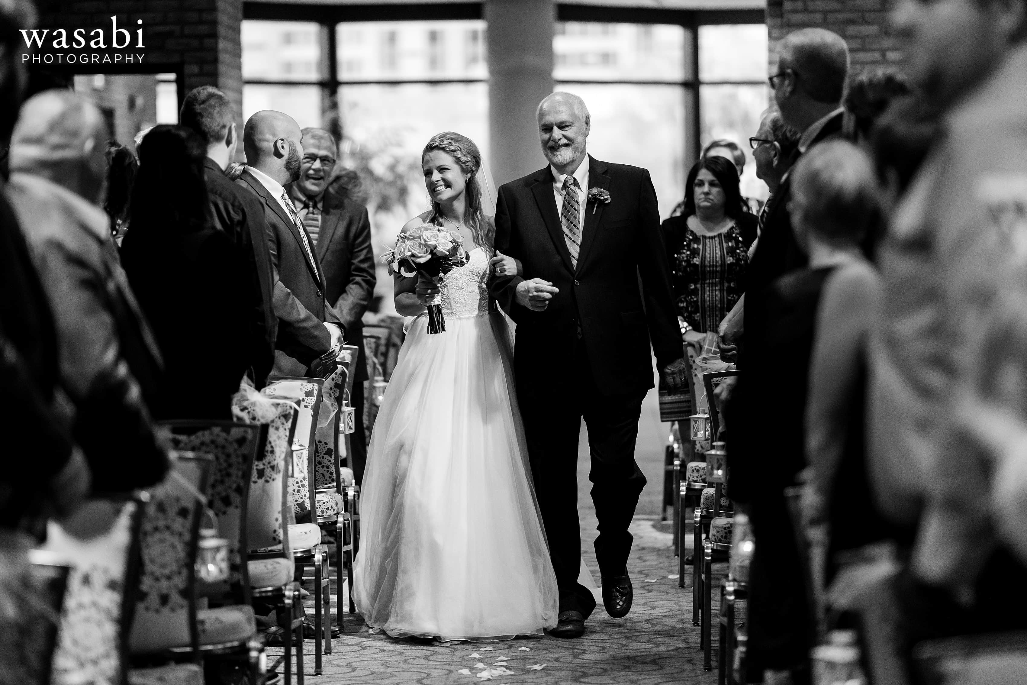 Bride and her father walk down the aisle during their wedding at Eberhard Center in downtown Grand Rapids