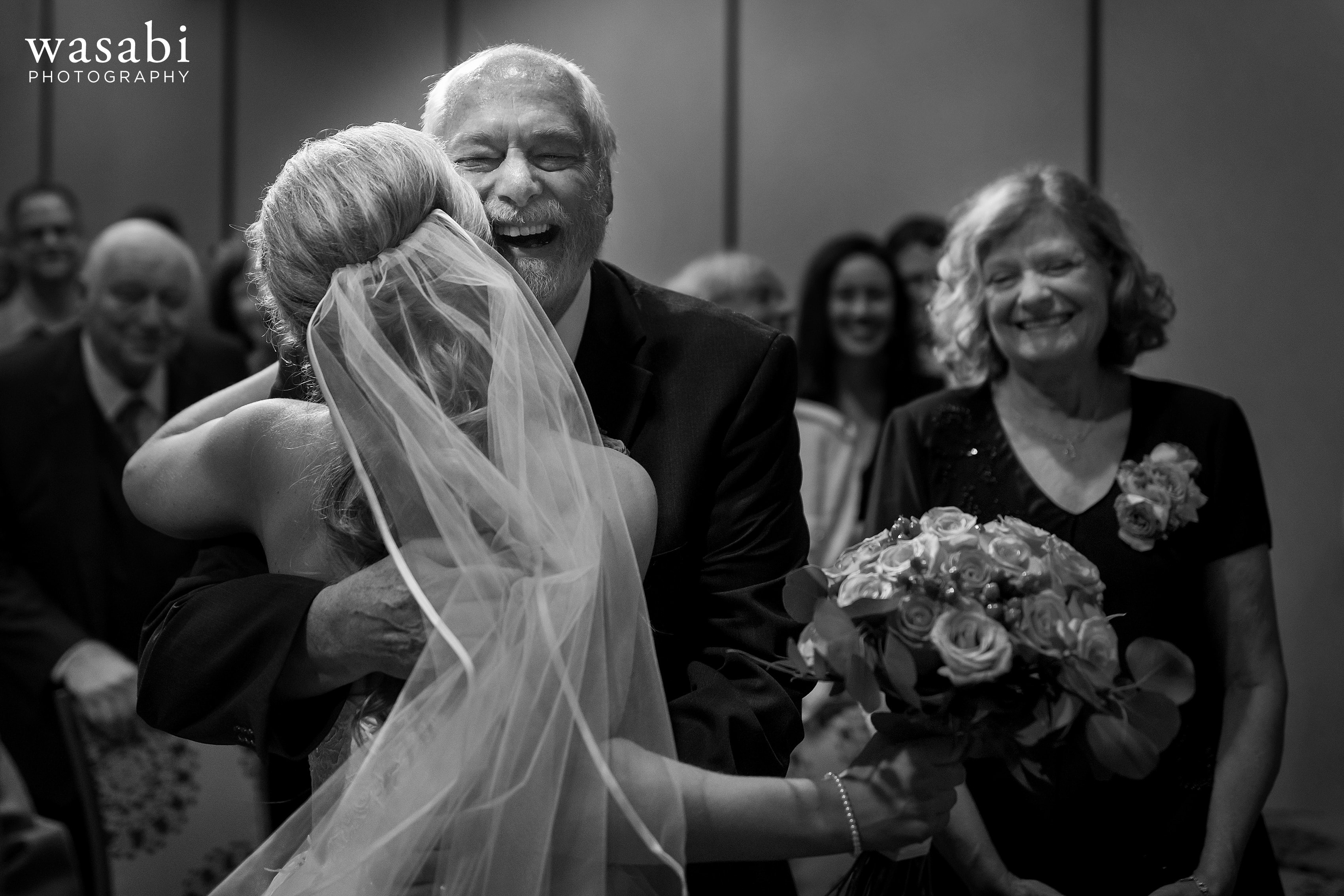 Bride hugs her father after walking down the aisle during their wedding at Eberhard Center in downtown Grand Rapids