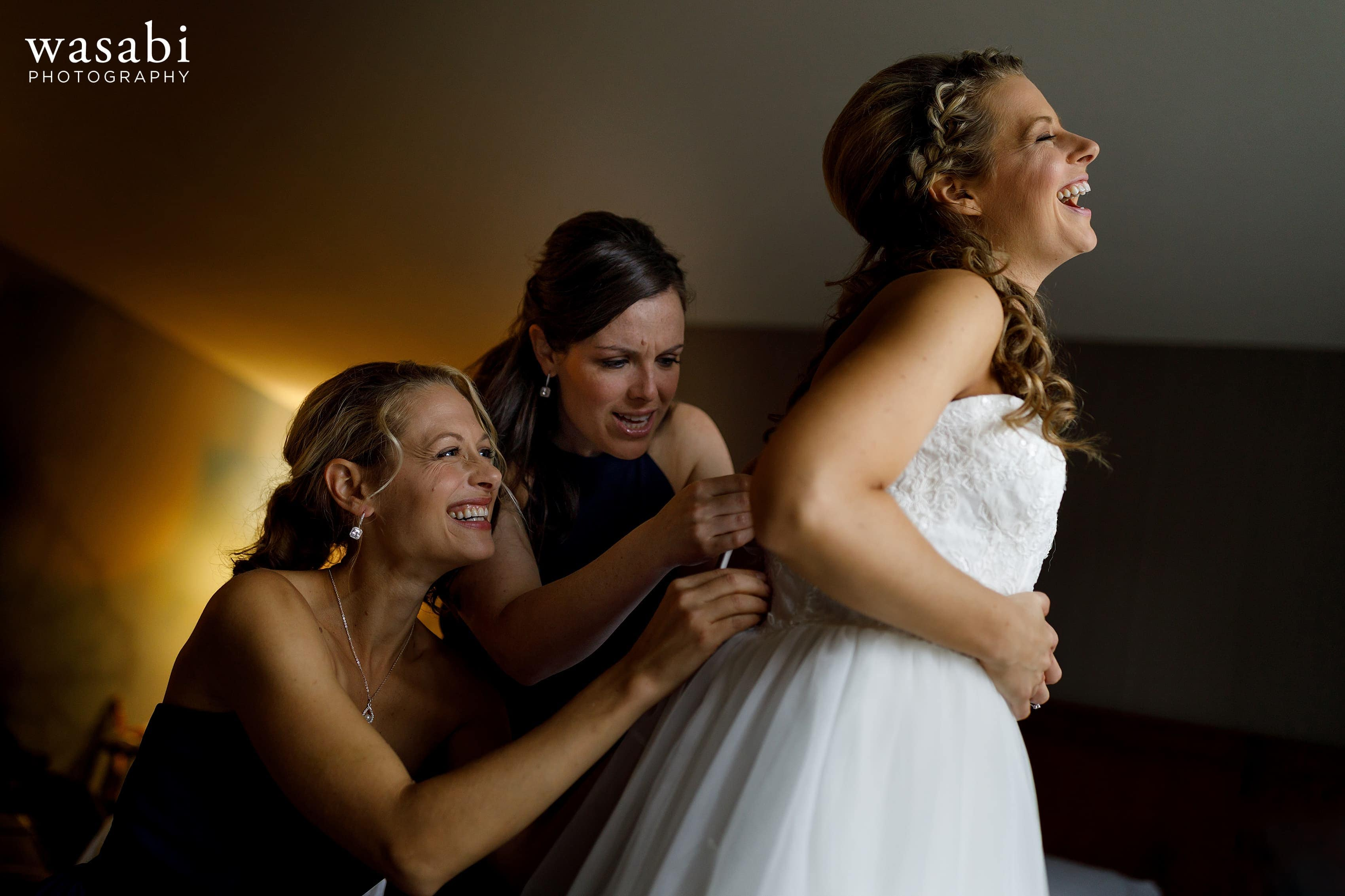 Bride laughs as bridesmaids help her into the dress at Courtyard Marriott Downtown Grand Rapids before her wedding