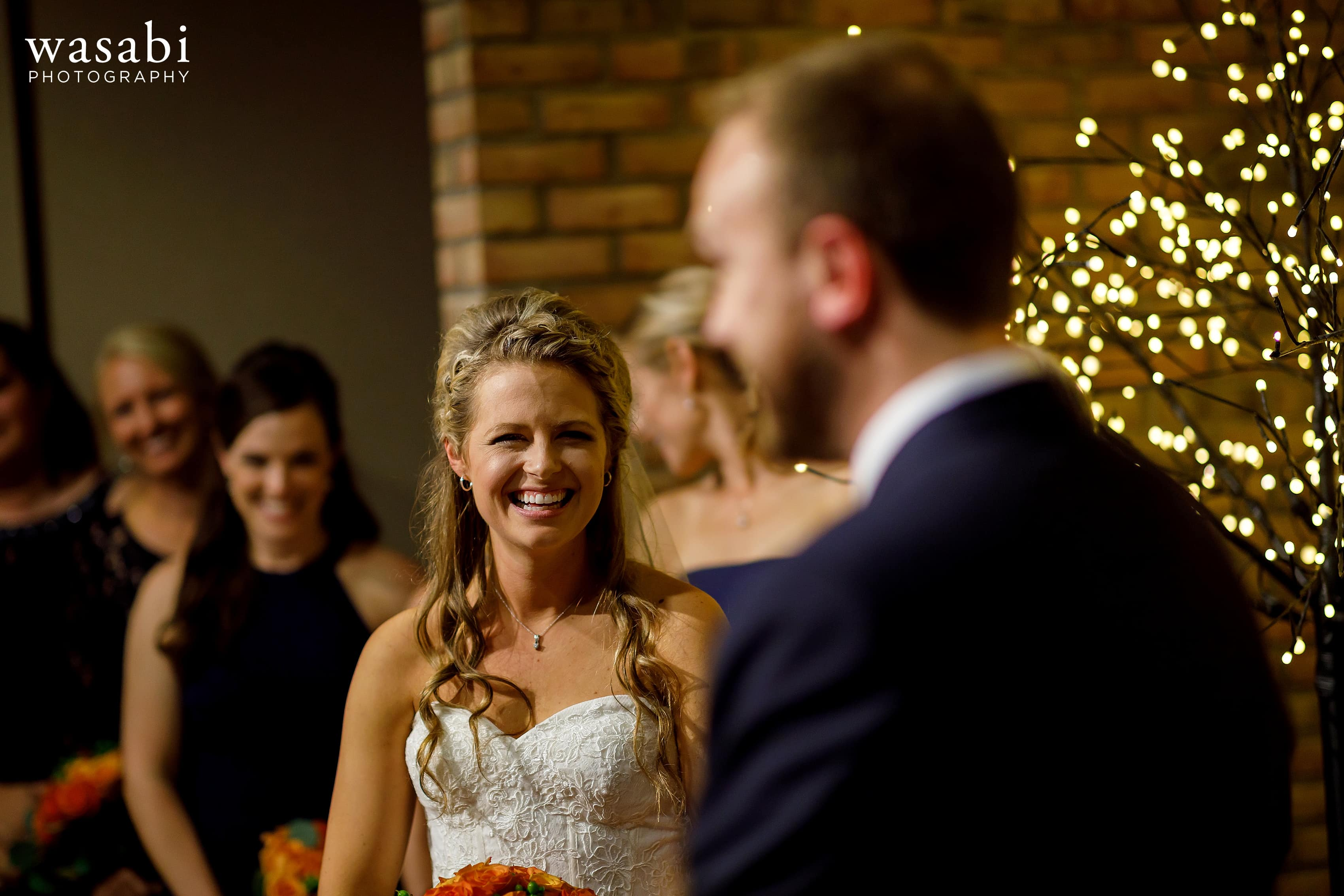 Bride smiles at groom during their wedding at Eberhard Center in downtown Grand Rapids