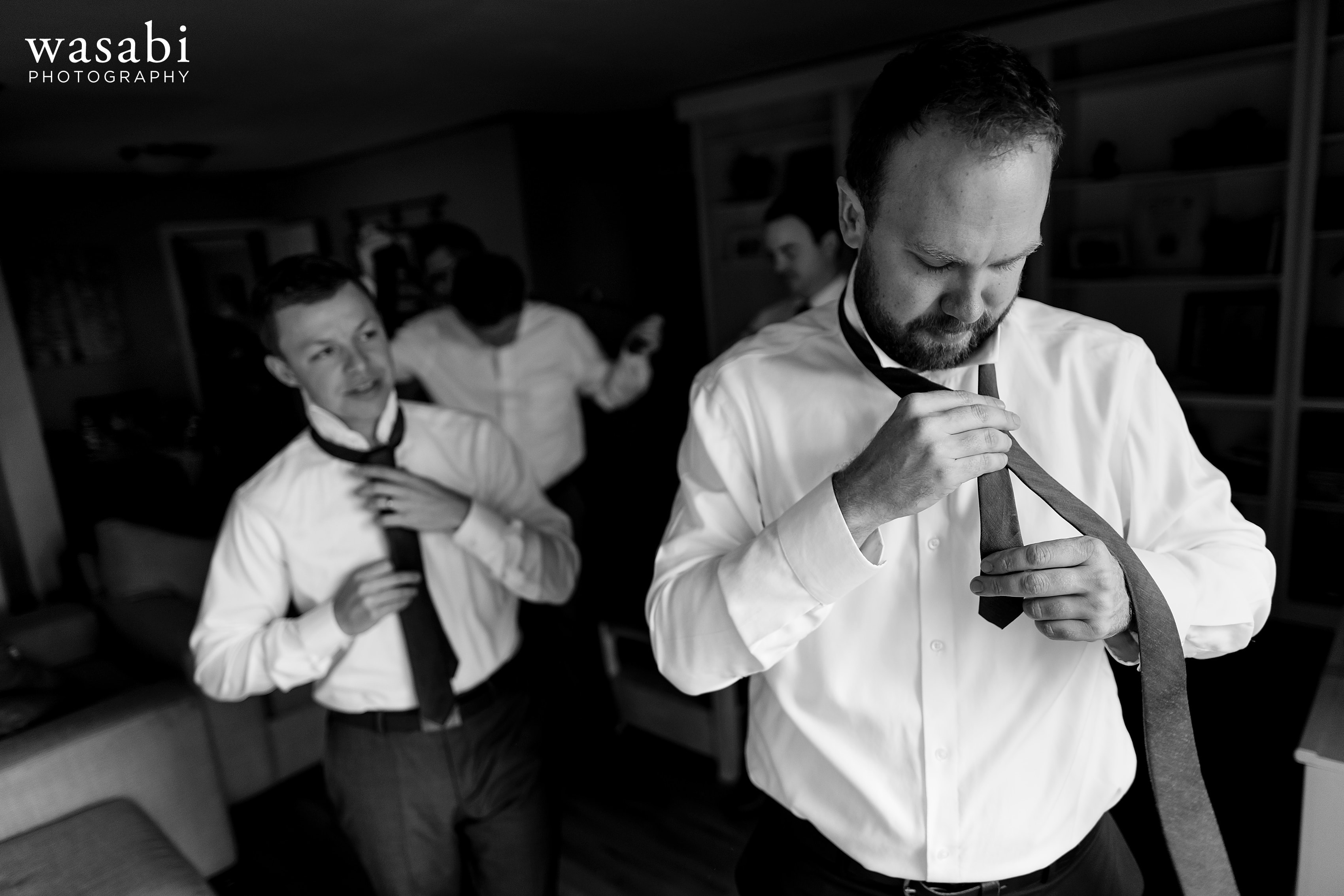 Groom does his tie with his groomsmen while getting ready for his Grand Rapids wedding