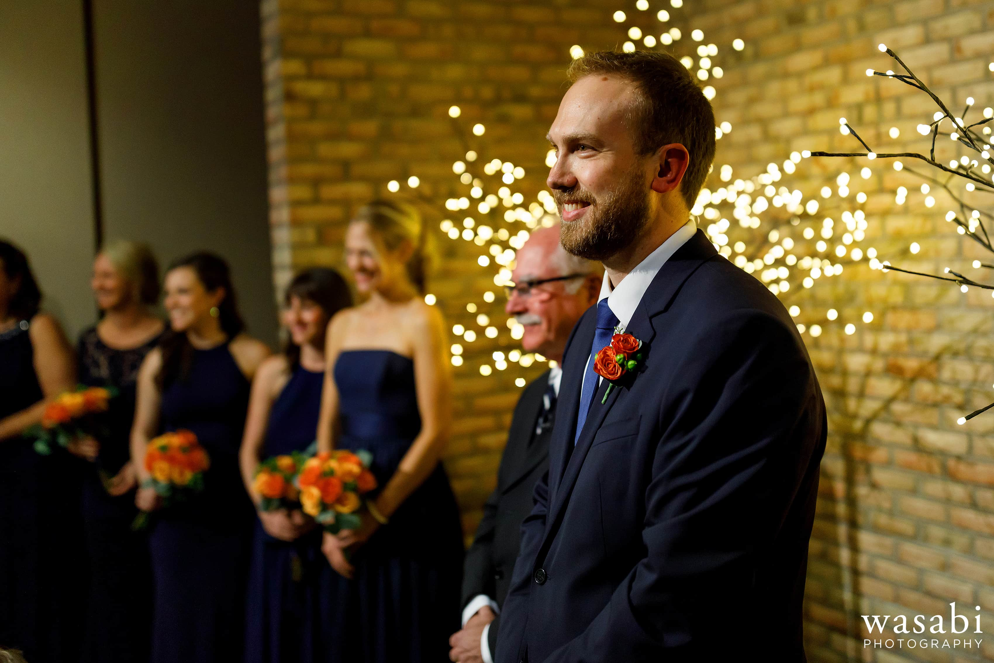 Groom watches as bride walks down the aisle during their wedding at Eberhard Center