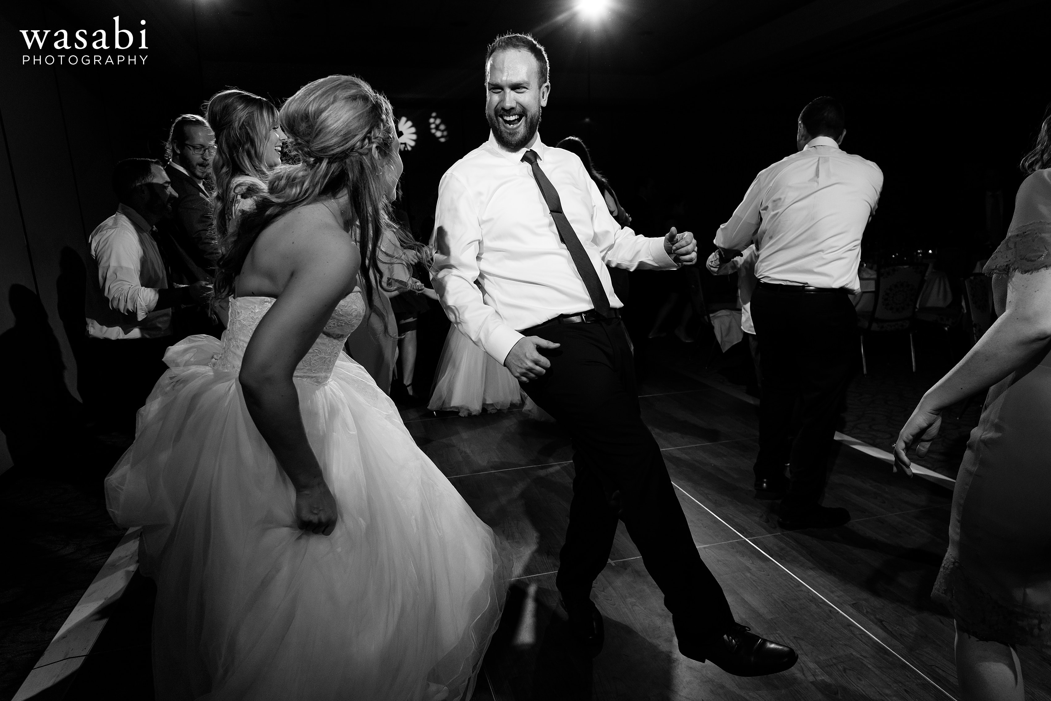bride and groom dance with guests during their Eberhard Center wedding reception