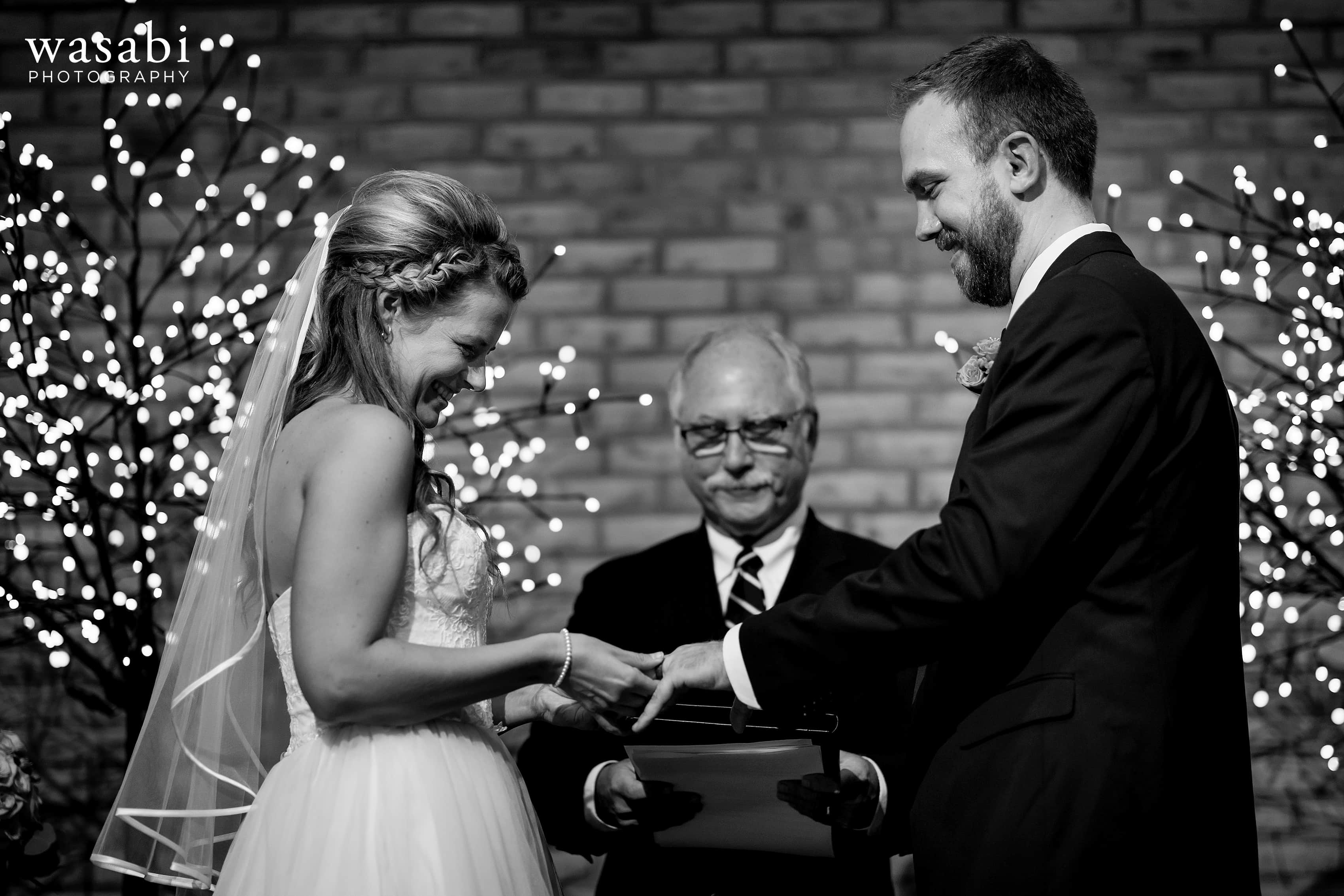 bride and groom exchange rings during their wedding at Eberhard Center in downtown Grand Rapids