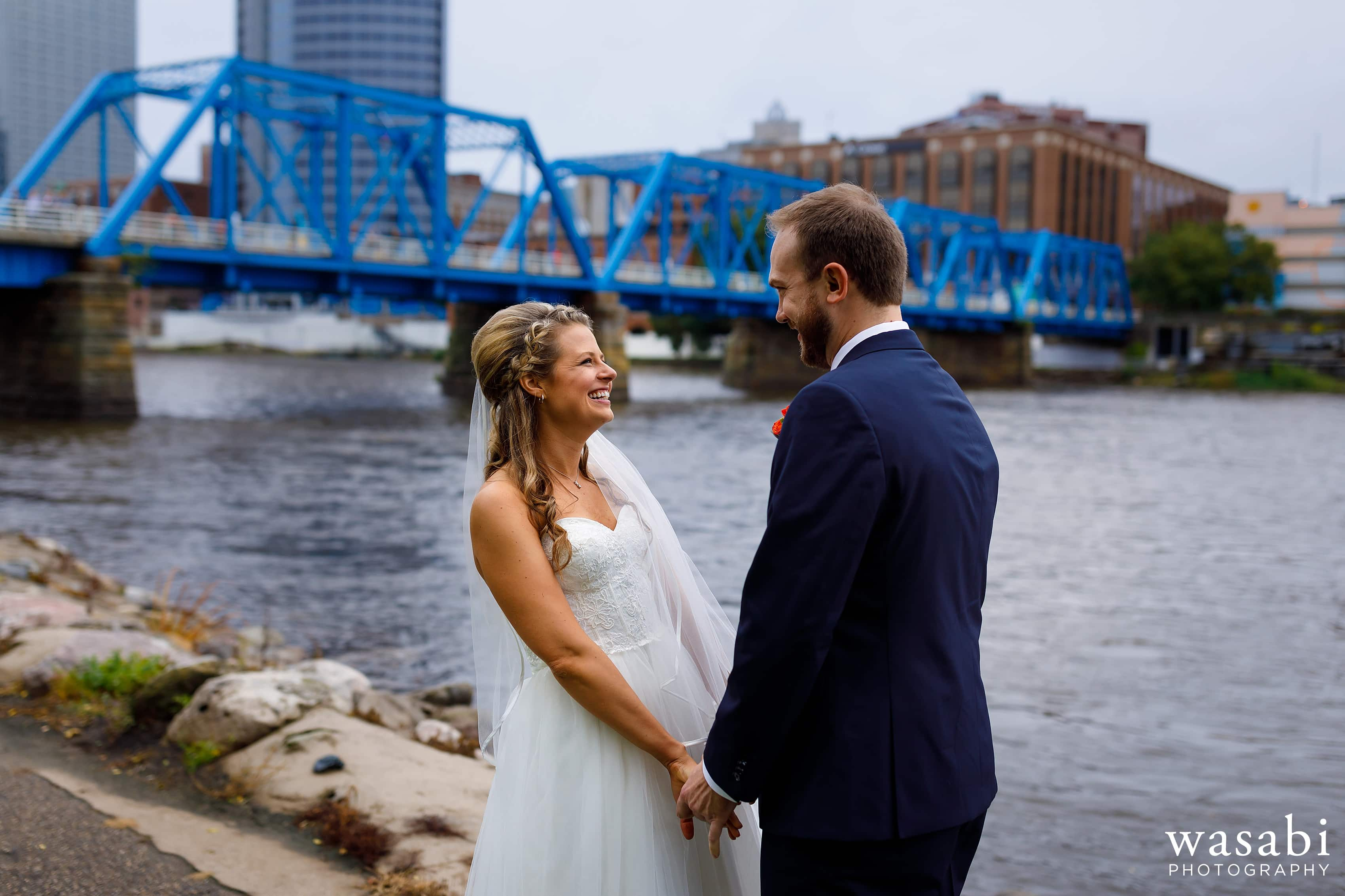 bride and groom first look on river by Blue Bridge in Grand Rapids