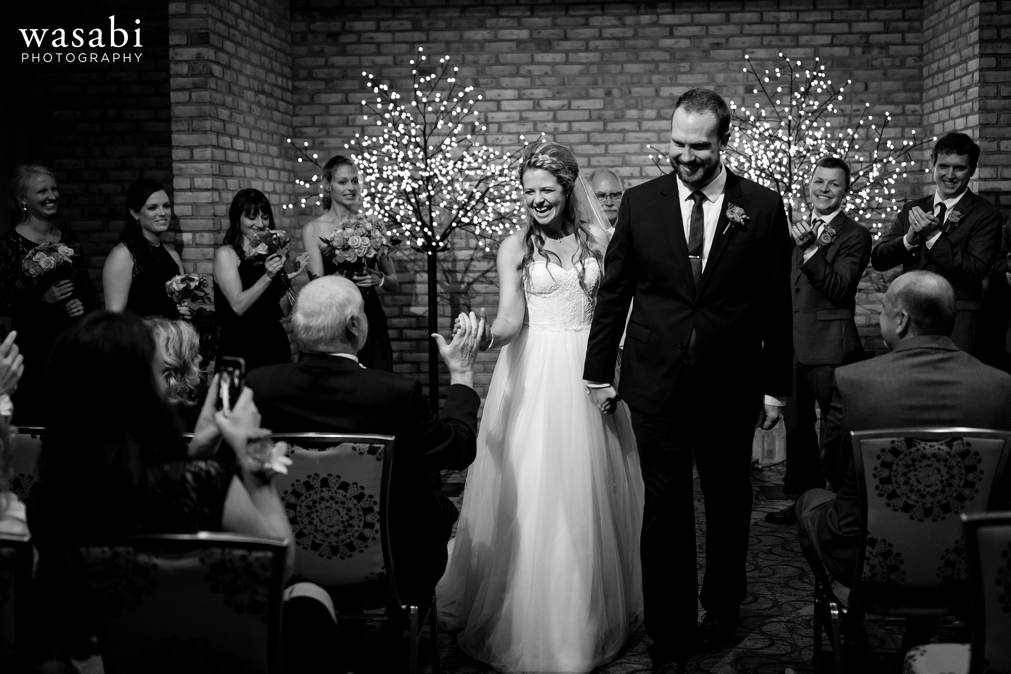 bride high fives her dad after their wedding at Eberhard Center in downtown Grand Rapids