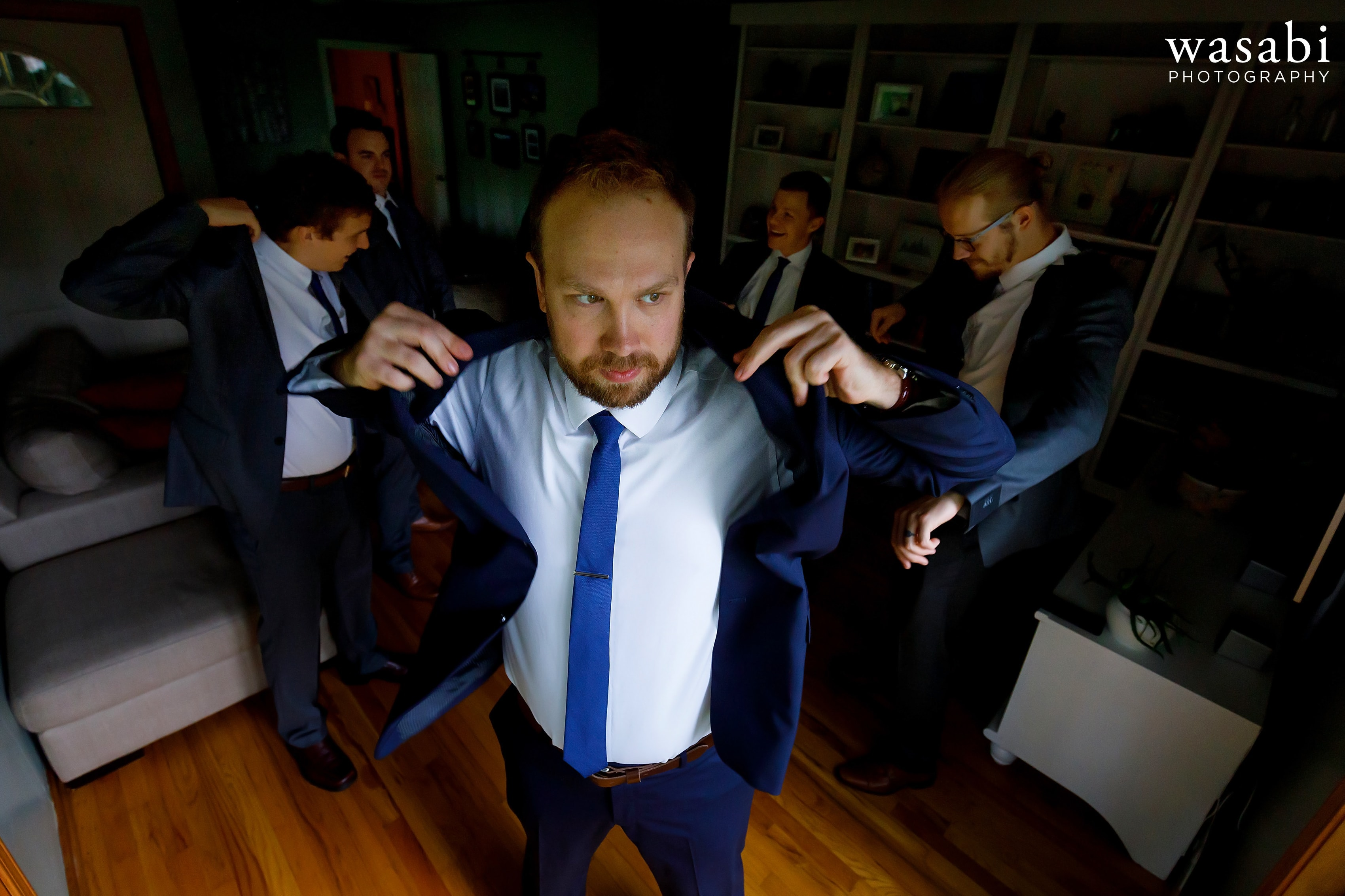 groom puts on his jacket with groomsmen in the background before his wedding