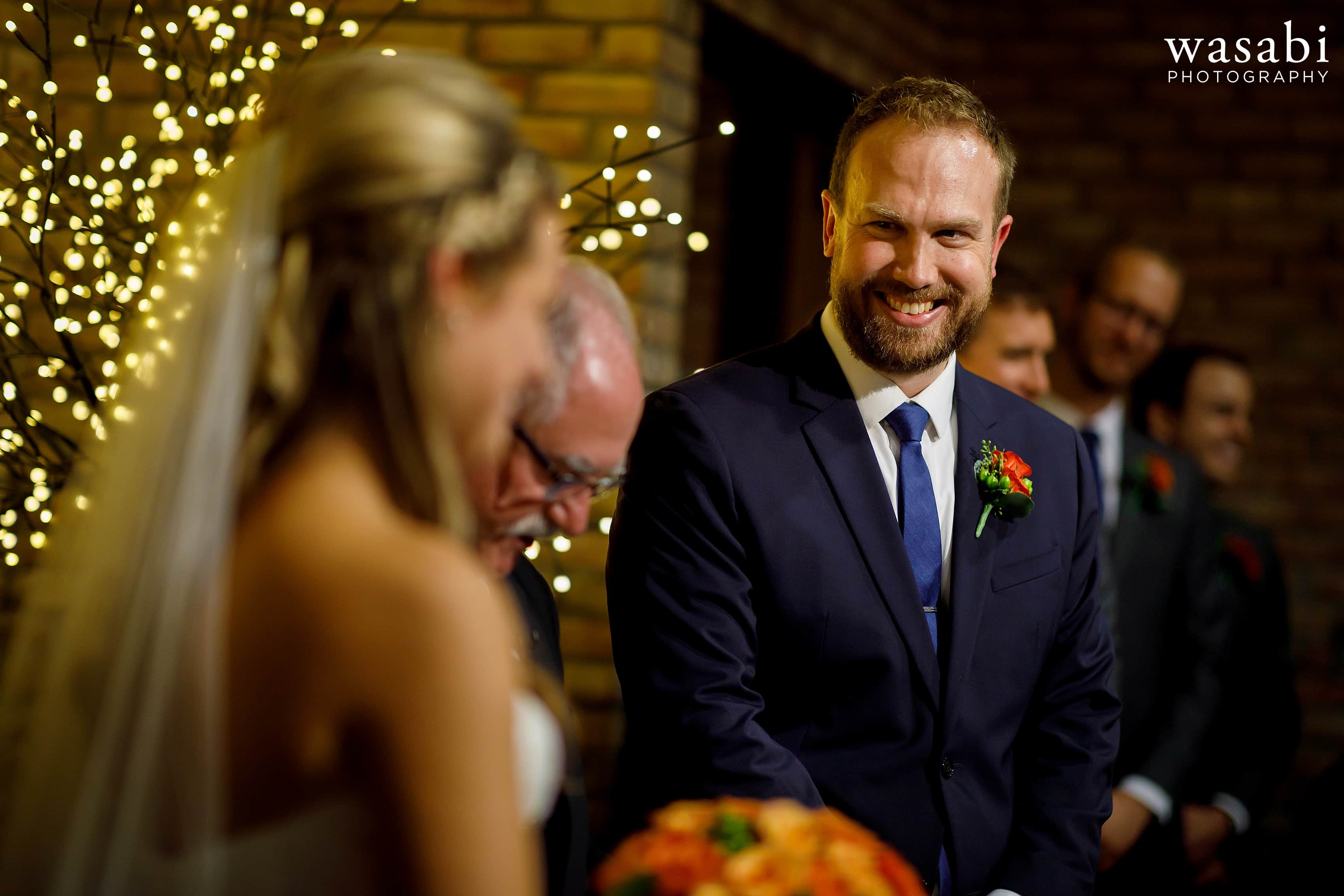 groom smiles at bride during their wedding at Eberhard Center in downtown Grand Rapids