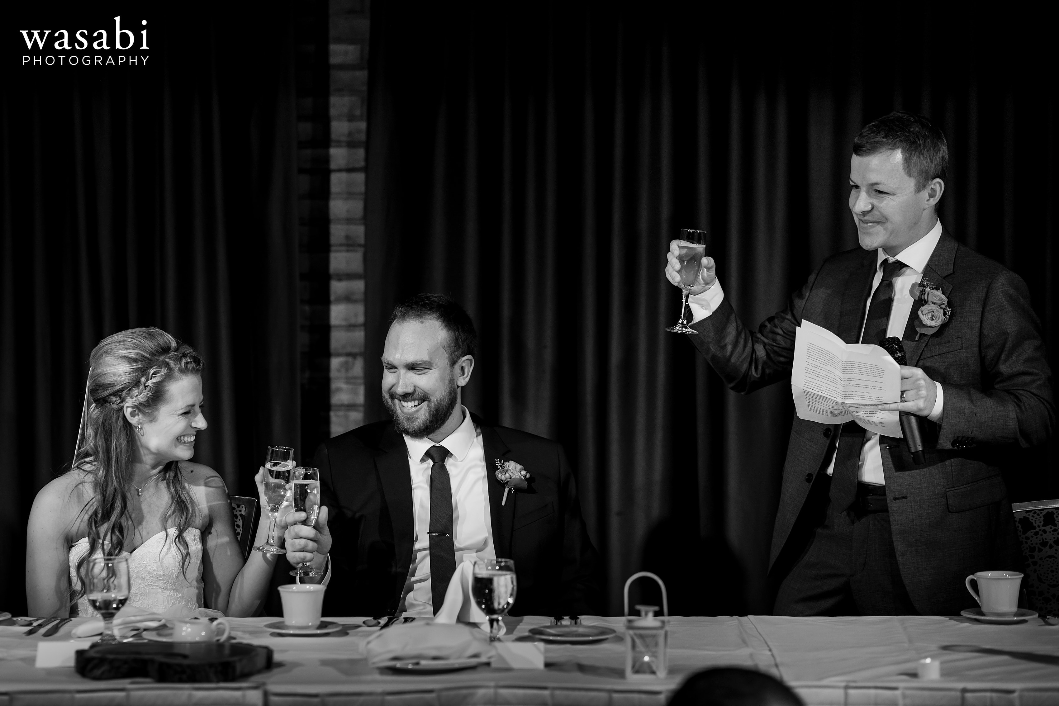 groomsman gives a toast during a wedding reception at Eberhard Center in downtown Grand Rapids