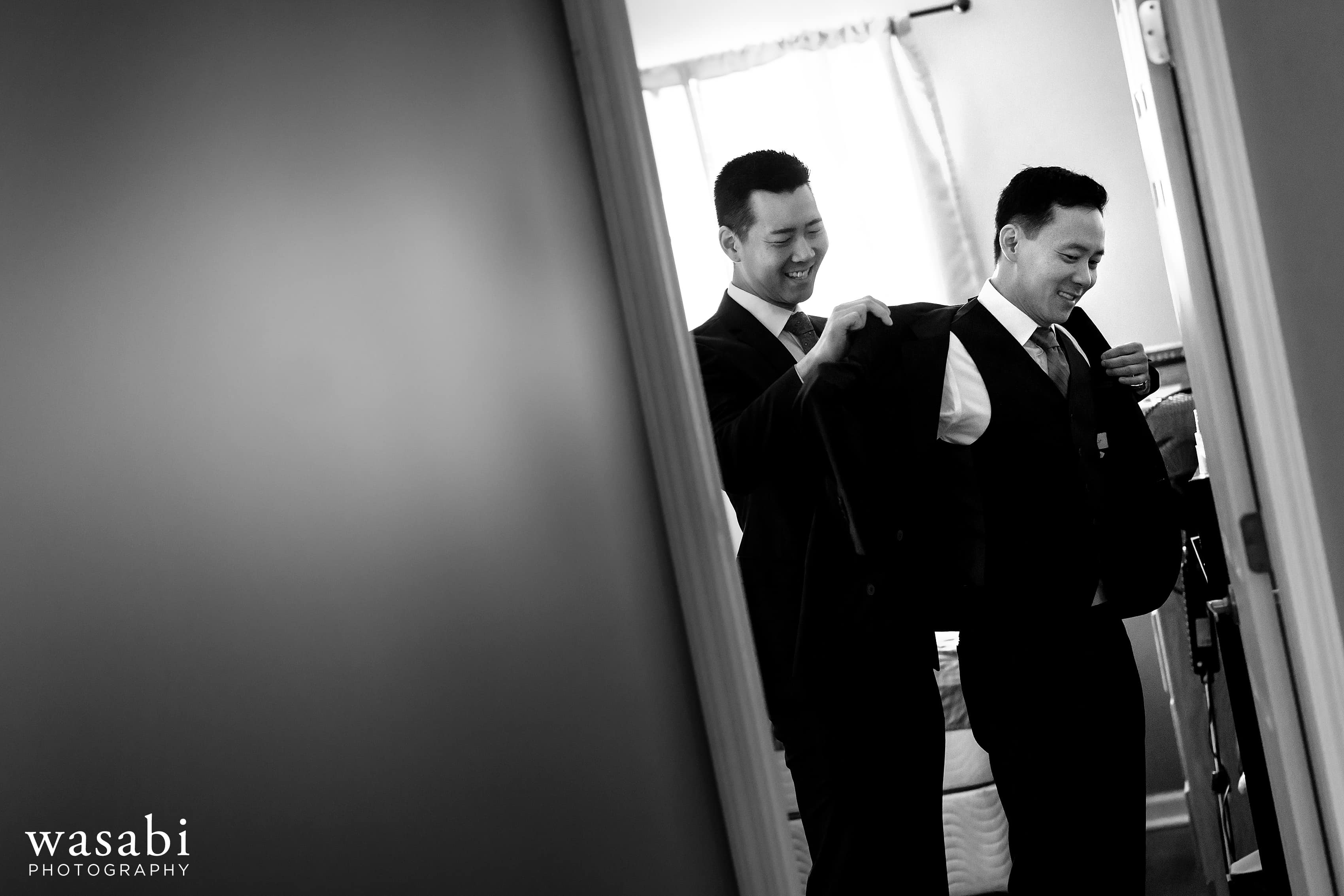 best man helps groom into suit jacket while getting ready for wedding