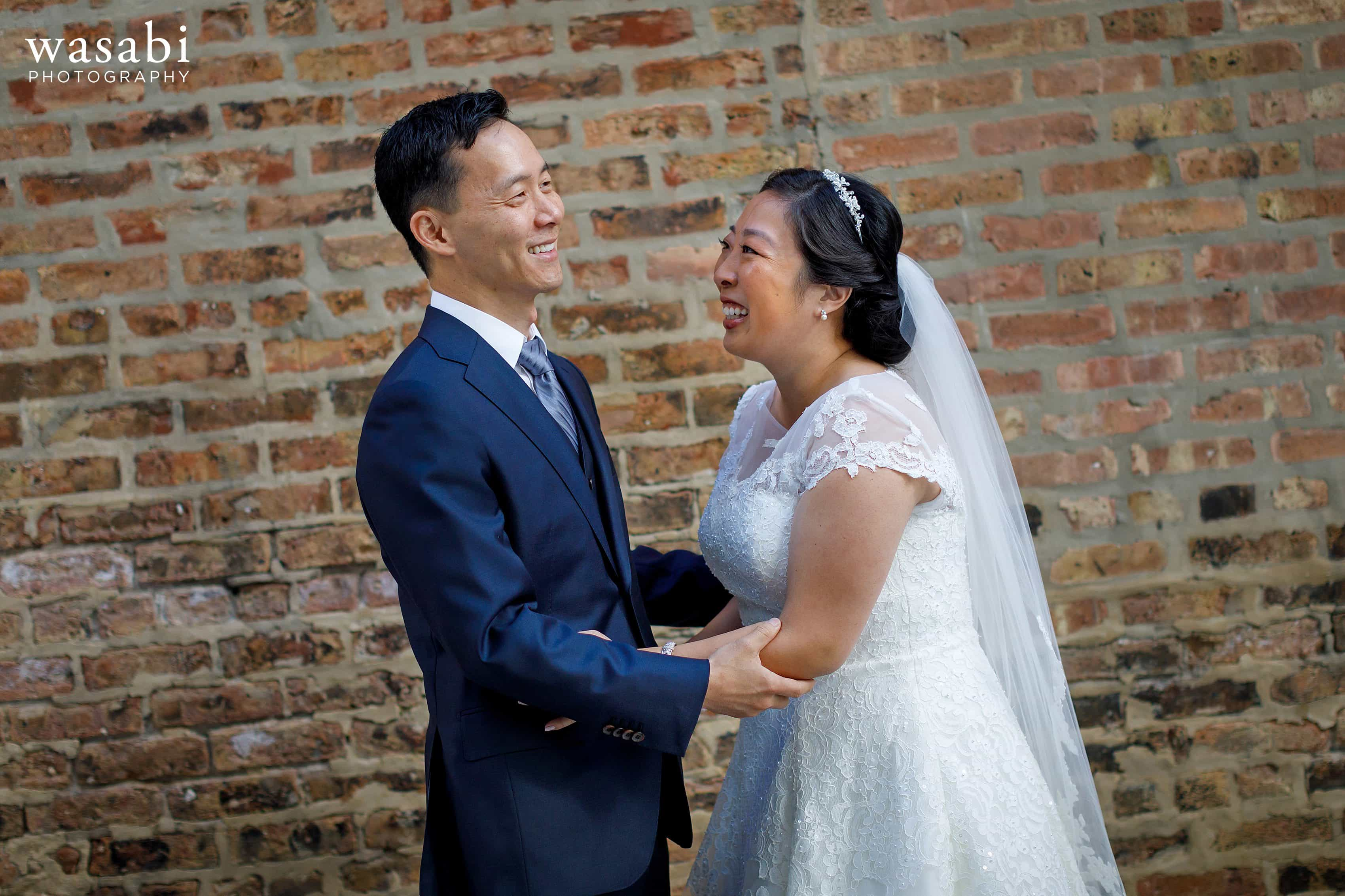 bride and groom laugh and smile during first look in alley with exposed brick wall in Chicago
