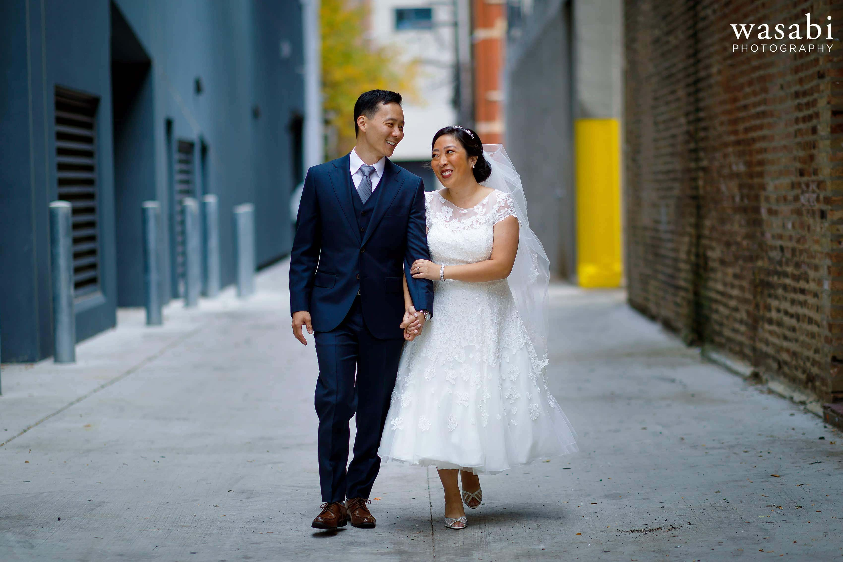 bride and groom laugh and smile while walking down alley during first look in alley with exposed brick wall in Chicago