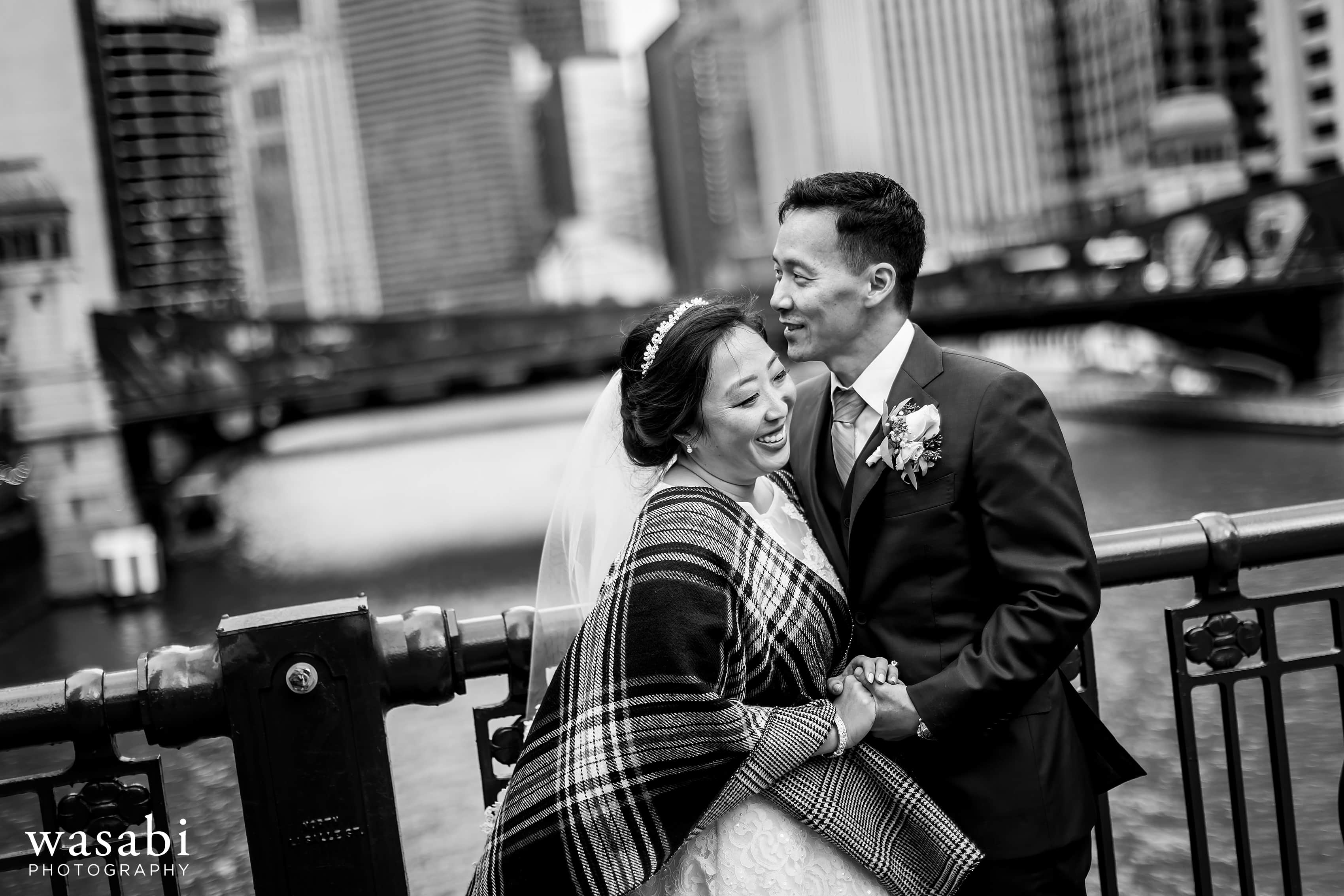 bride and groom laugh during portraits on LaSalle Street Bridge in Chicago following their wedding