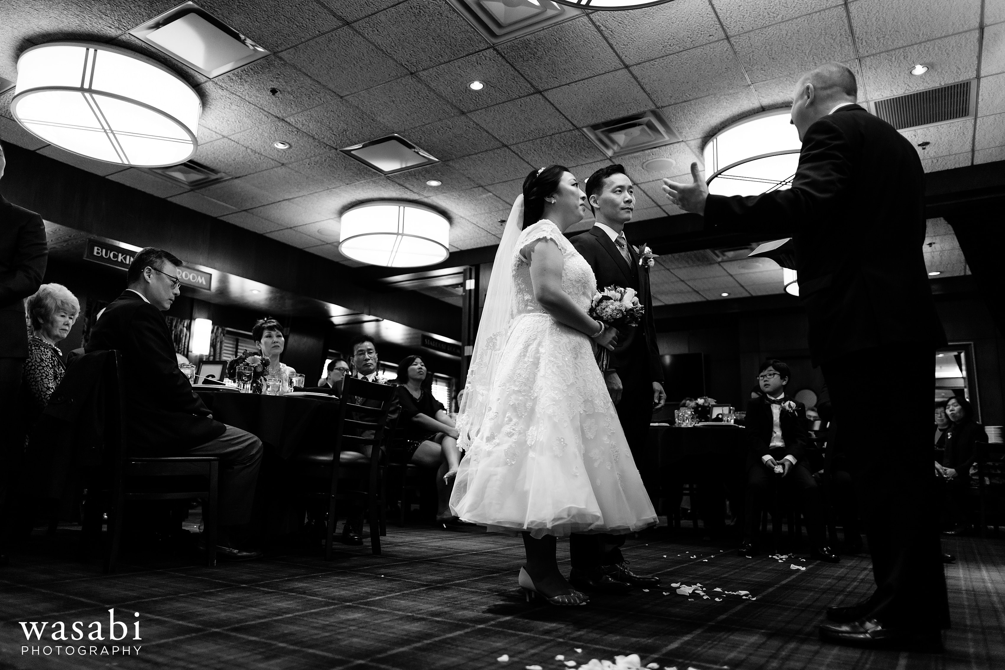 bride and groom listen to officiant during Wildfire Restaurant wedding ceremony in Chicago