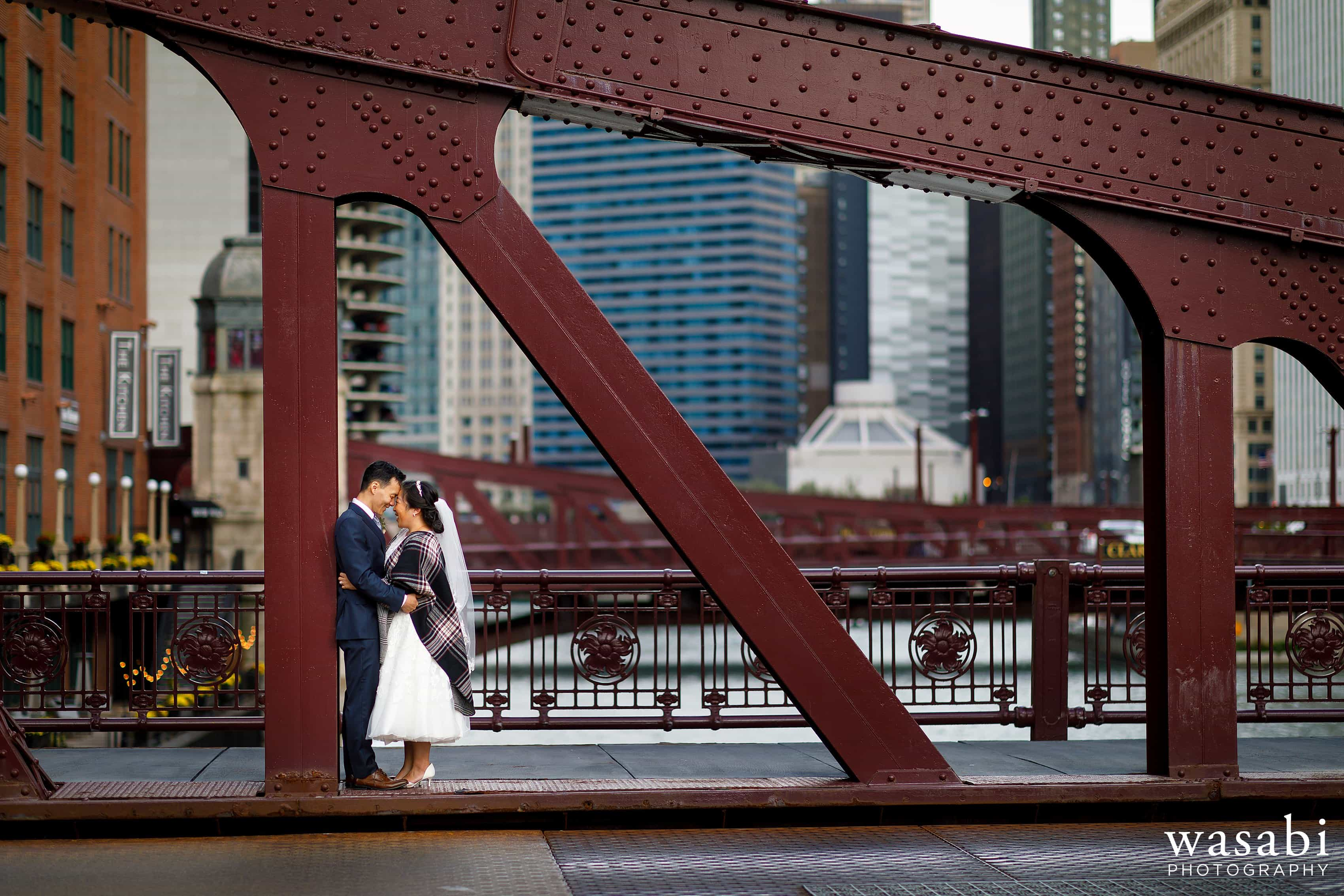 bride and groom pose for a portrait along sidewalk on LaSalle Street Bridge in Chicago following their wedding