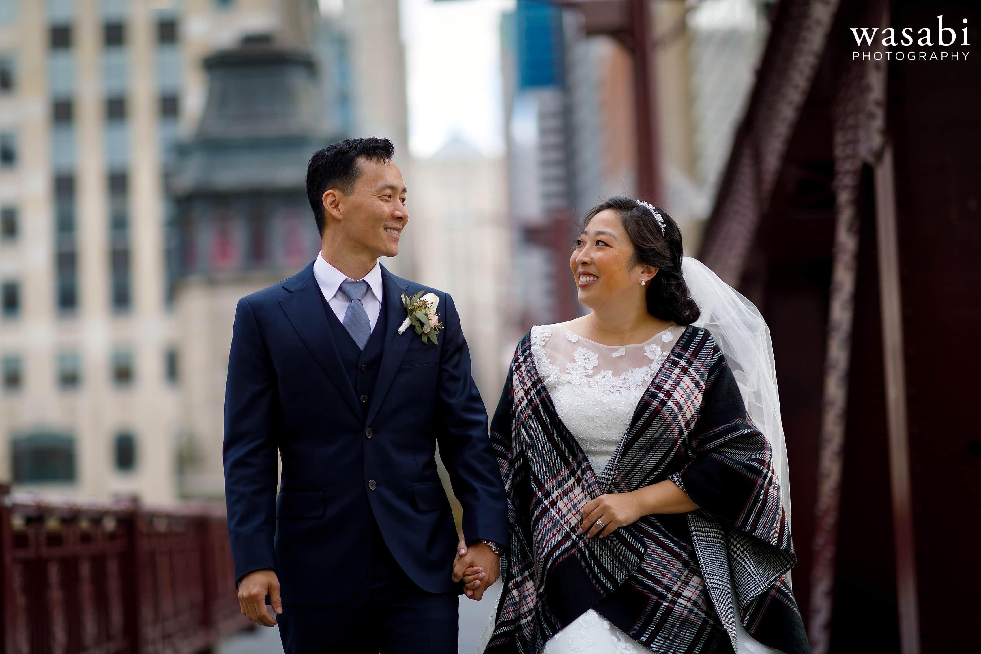 bride and groom walk along sidewalk on LaSalle Street Bridge in Chicago following their wedding
