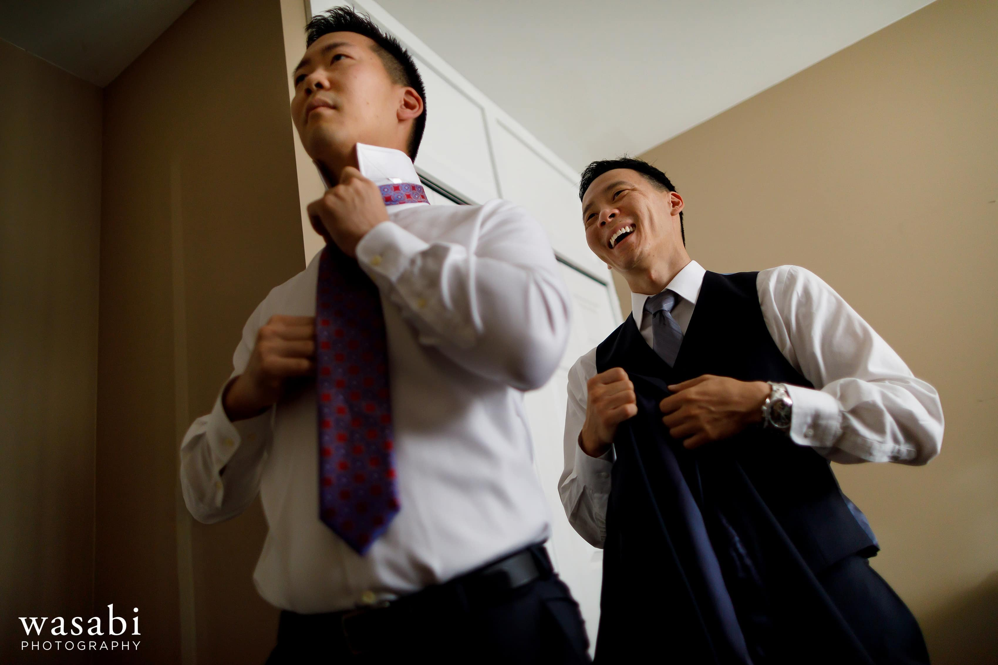 groom and best man laugh while adjusting ties and getting ready for wedding