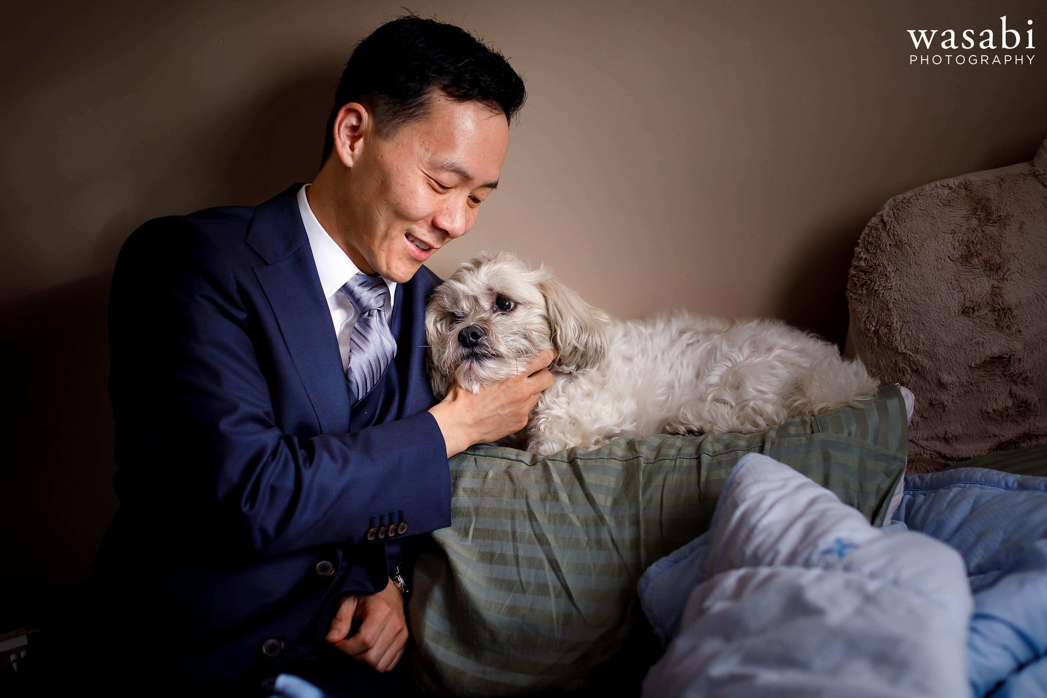 groom and dog while getting ready for wedding