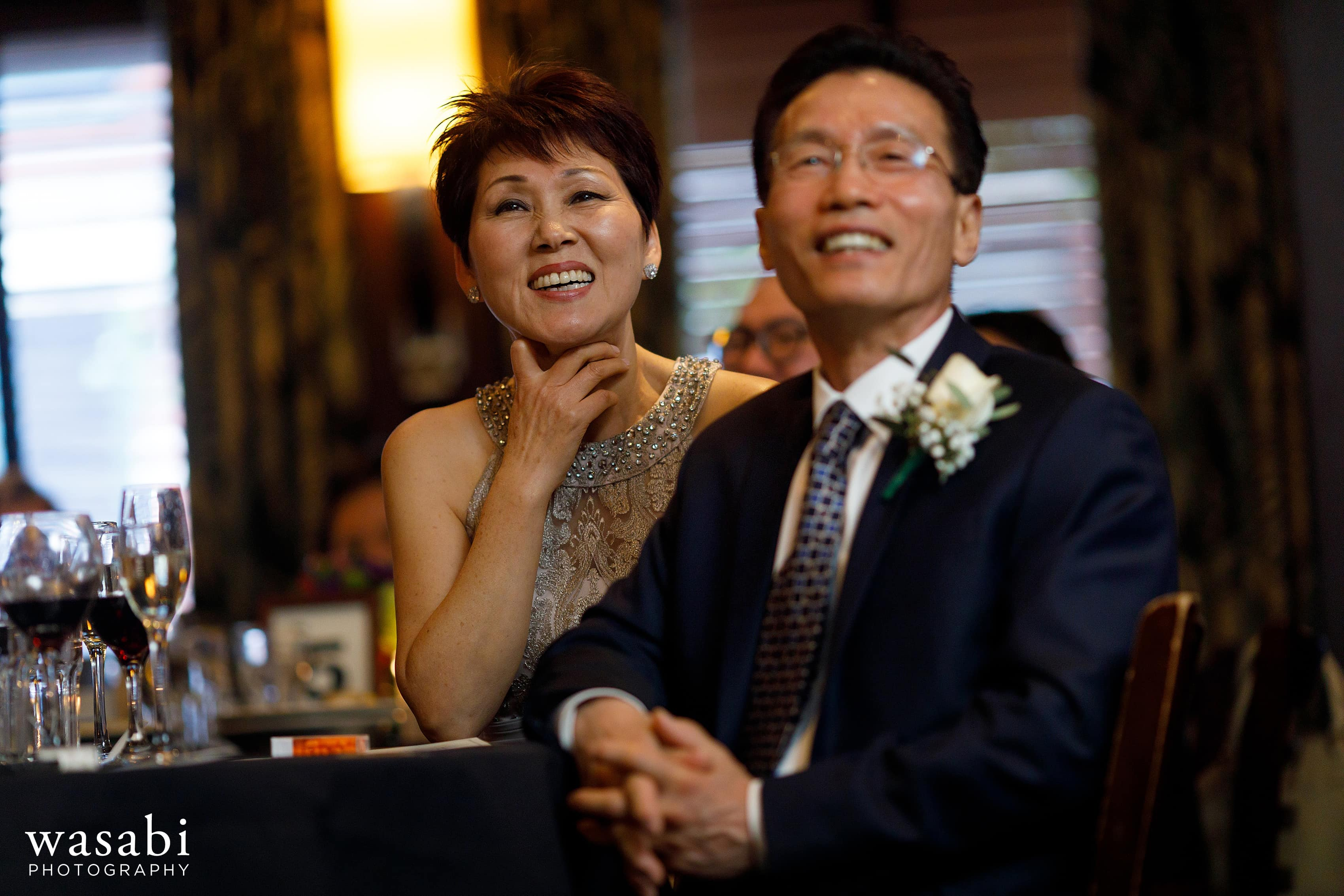 mother and father of the groom smile and laugh during toasts at Wildfire Restaurant wedding reception in Chicago
