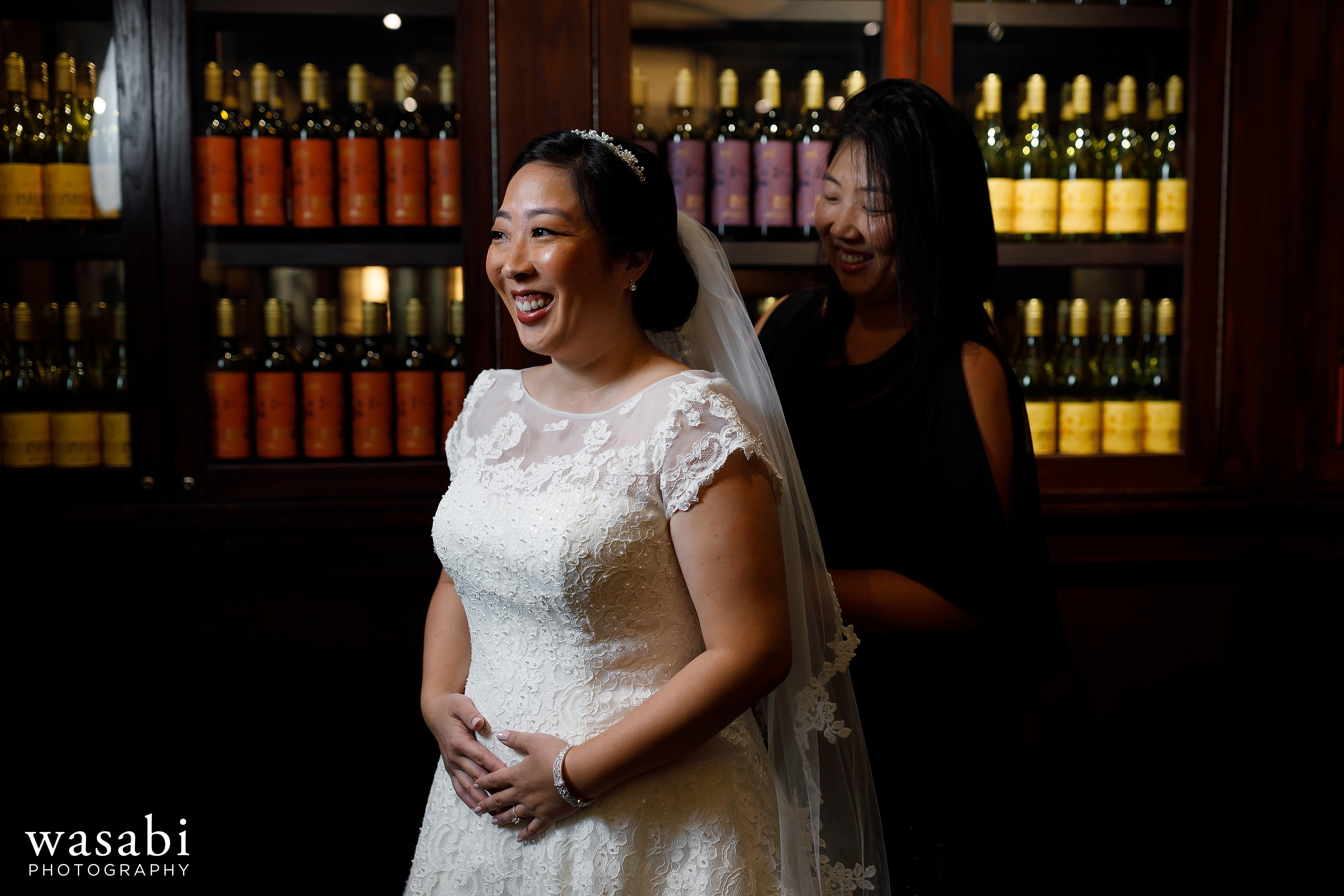 sister helps bride into wedding dress